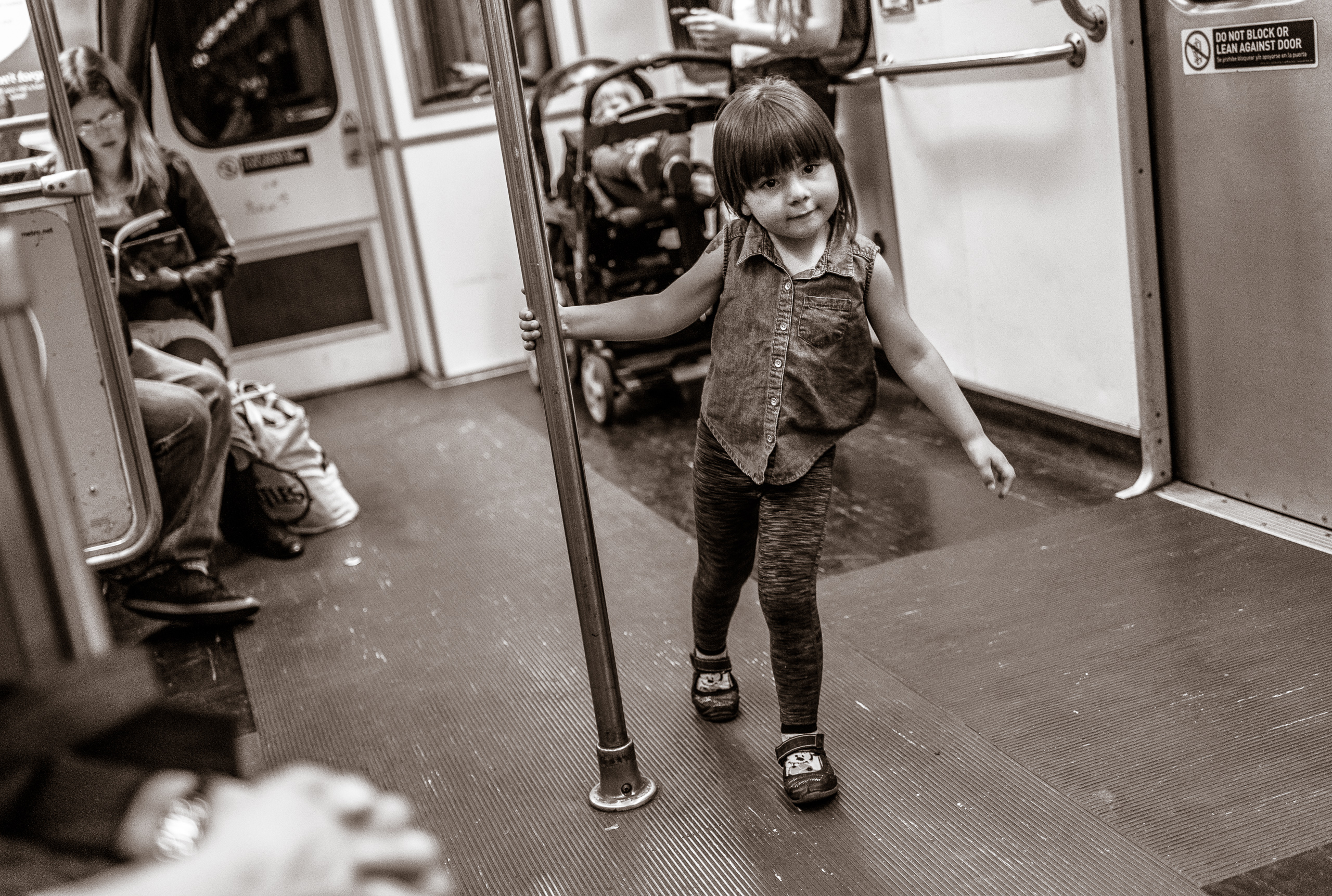 a young girl uses the center pole of the subway train car as a sort of Maypole to spin around as she plays and dances