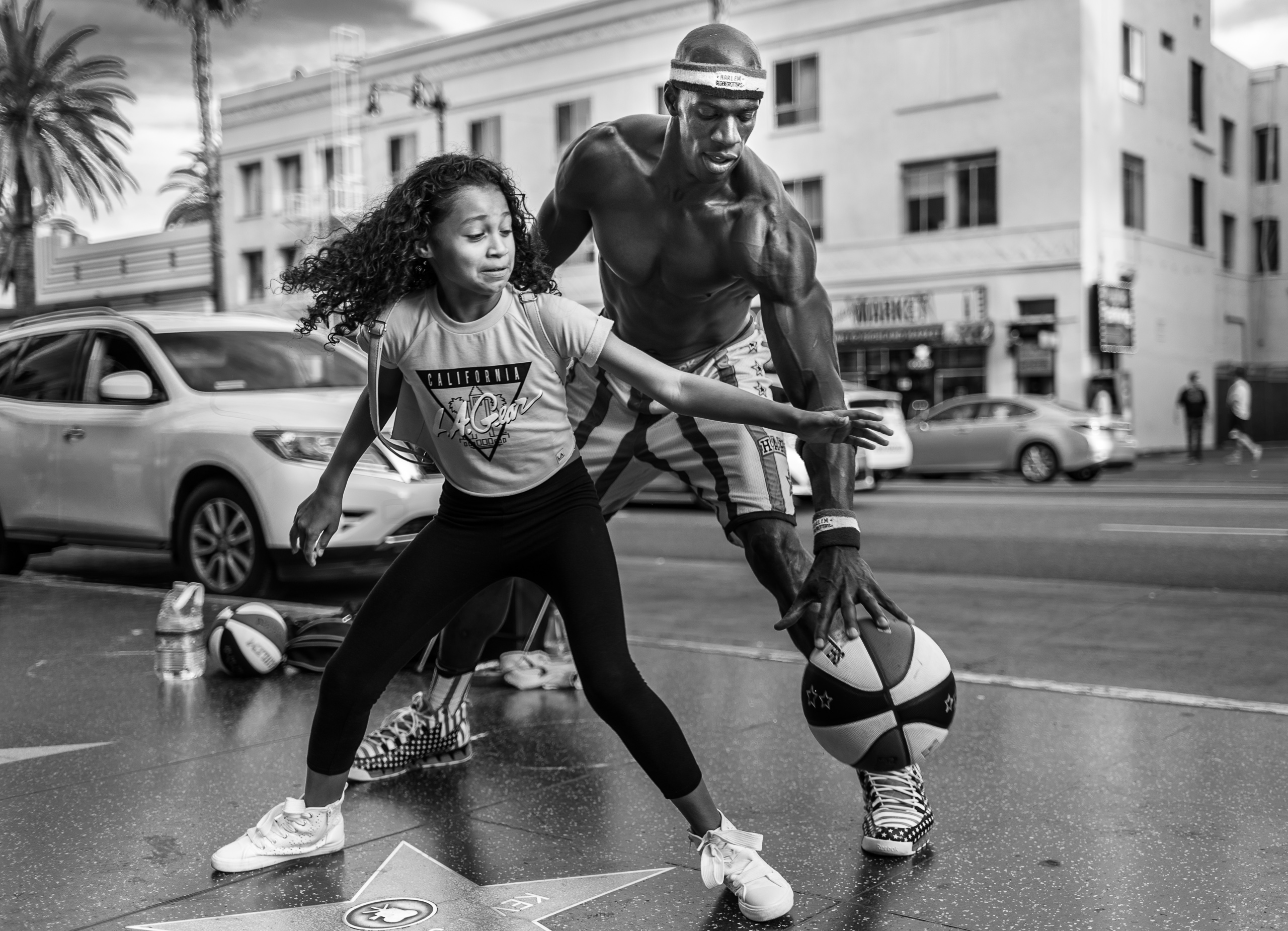 """a """"Michael Jordan"""" character on  Hollywood Blvd plays 1-on-1 with a young girl who tries in vain to take the ball away from him"""