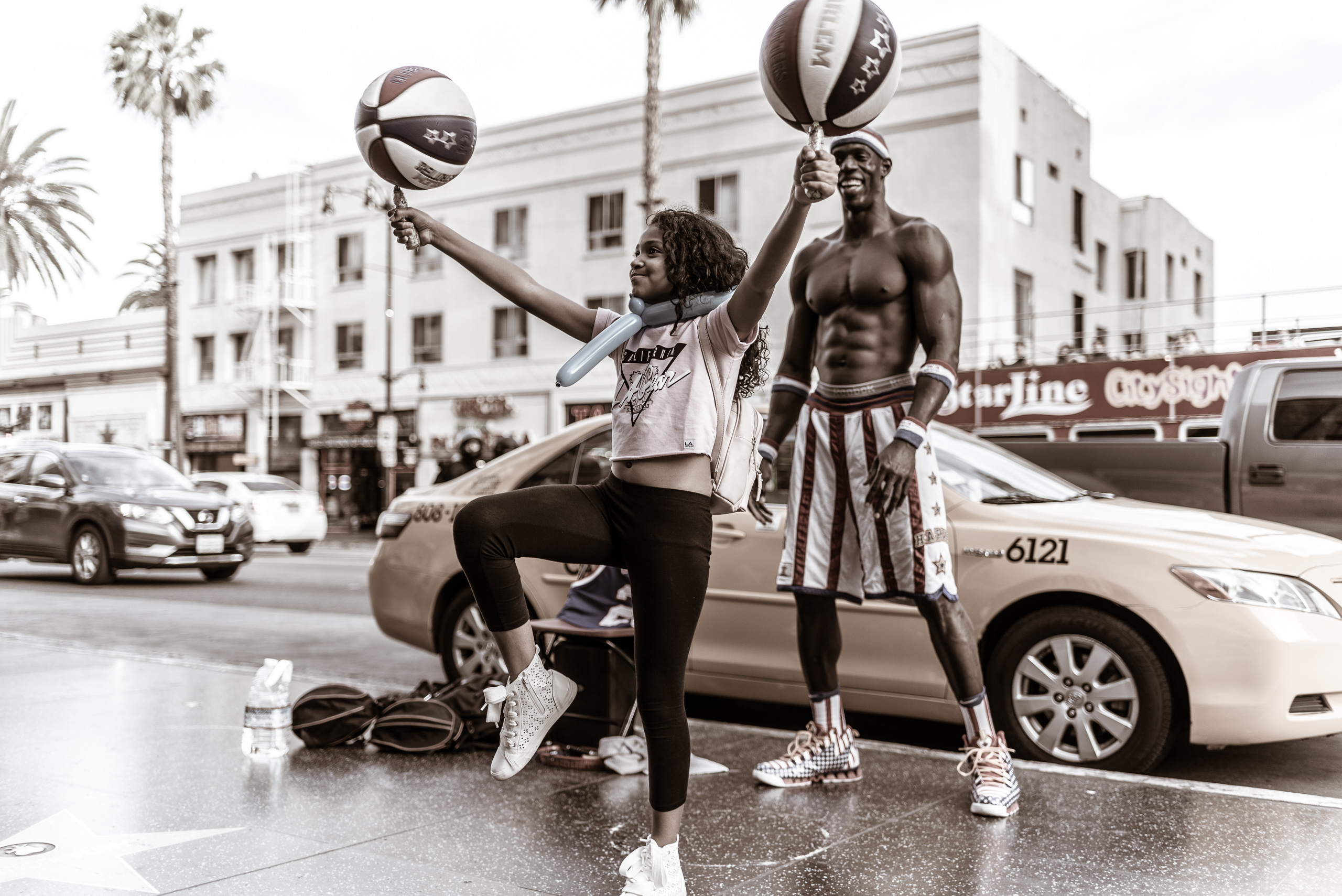 """""""Michael Jordan"""" stands behind a girl who has a basketball spinning in each outstretched hand as she stands on one foot. Hollywood Blvd, on the Walk of Fame sidewalk at Hollywood & Highland"""