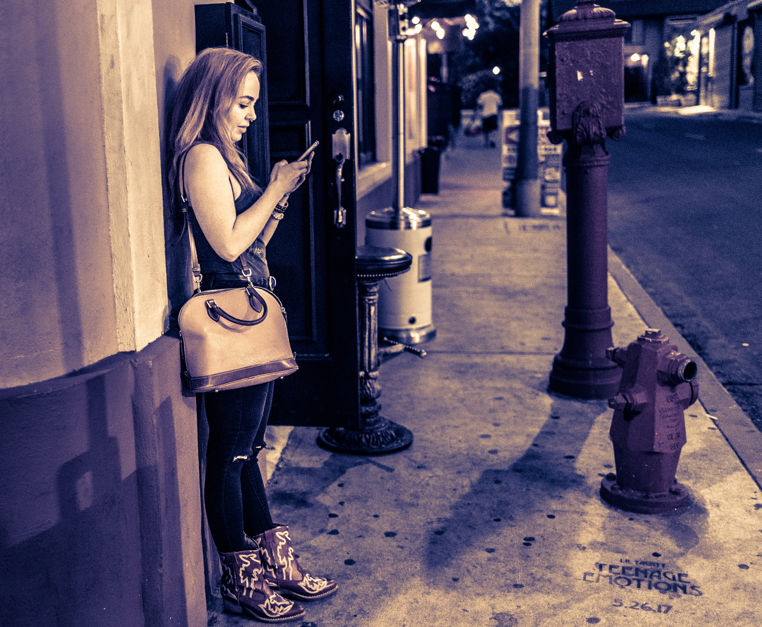 a woman in red boots leans in to the side of a building and checks her cell phone around the corner from Hollywood Blvd.