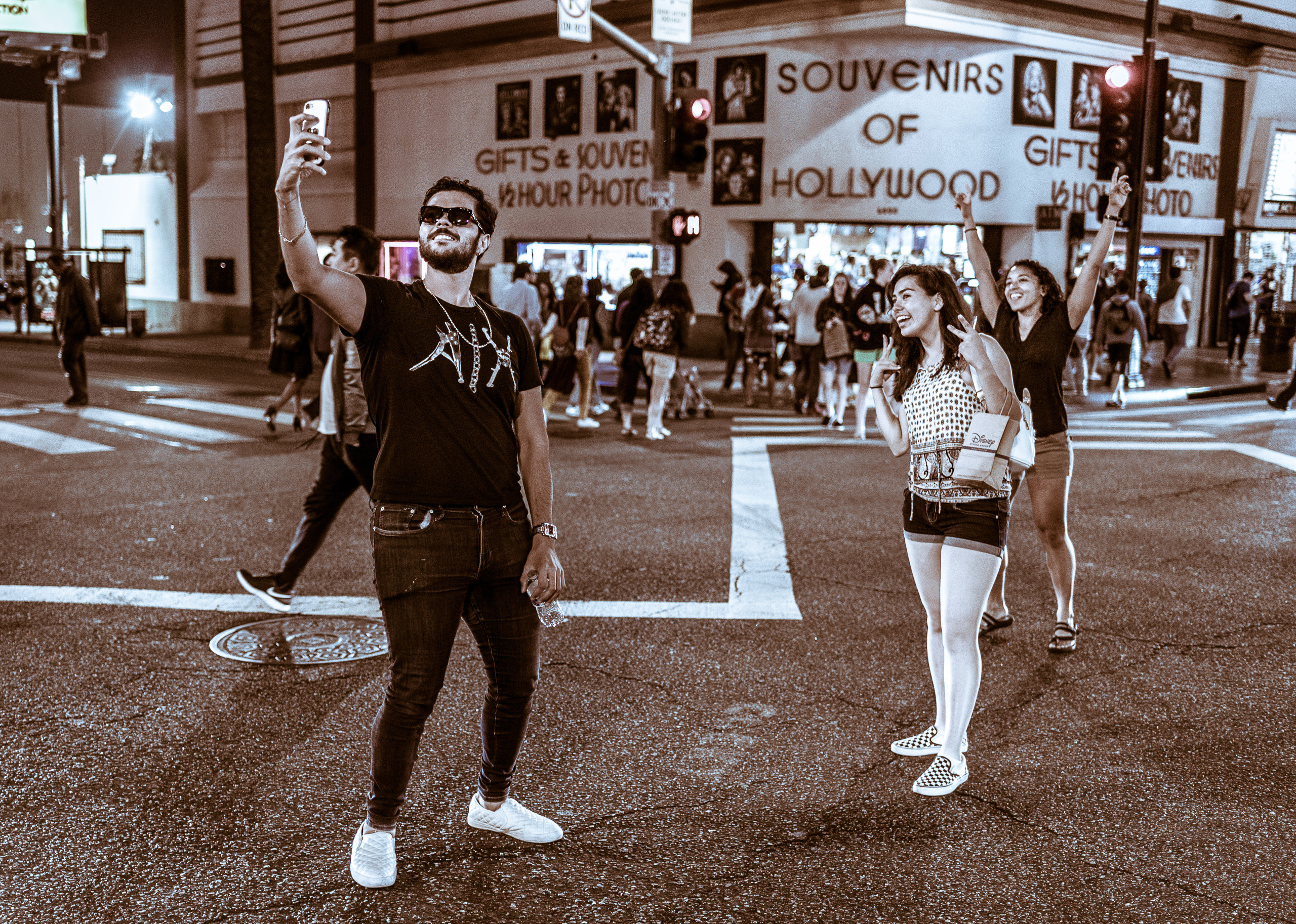 a man stands in the middle of the intersection at Hollywood & Highland and holds his cell phone high in the air. Behind him, two women raise their arms in a sort of exalted victory gesture