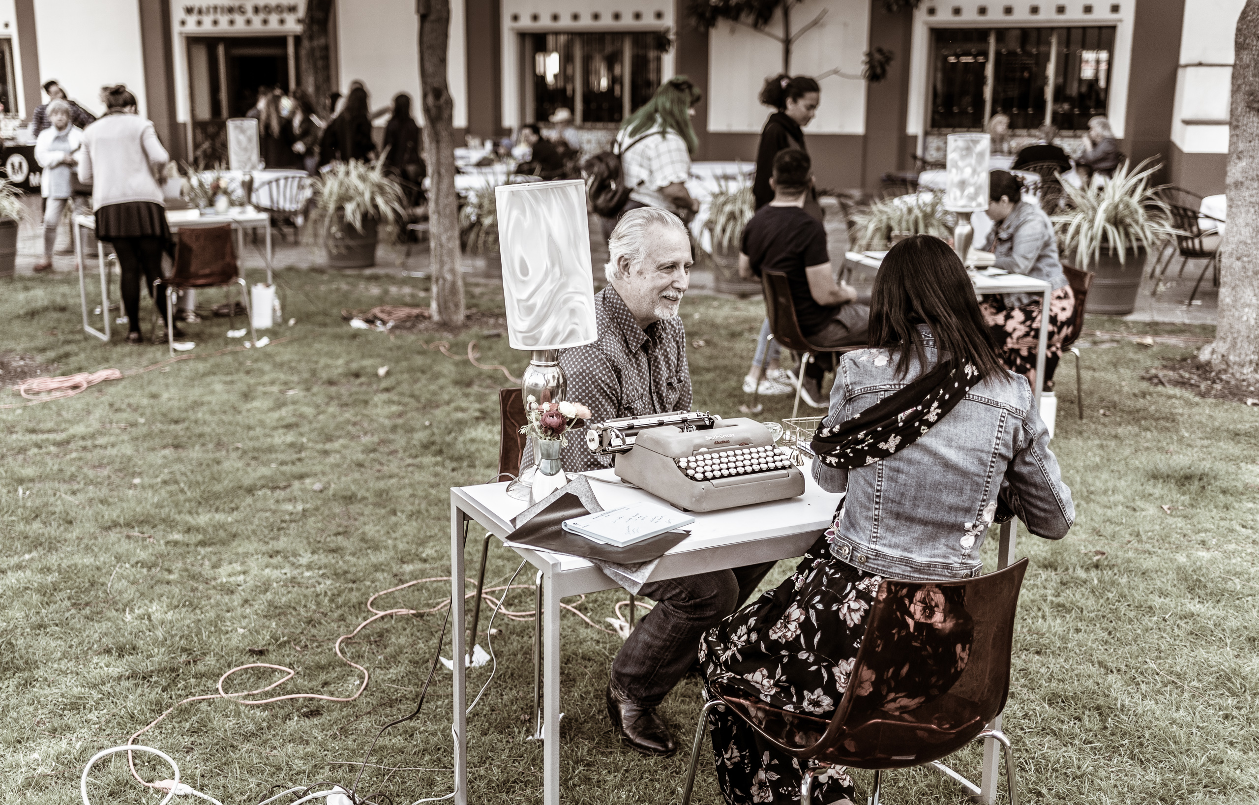 "a poet and a guest sit across a table on the North Patio at Union Station in Los Angeles. As part of ""The Poet is in"" for National Poetry Month, poets have a conversation with a guest and then write a poem for them."
