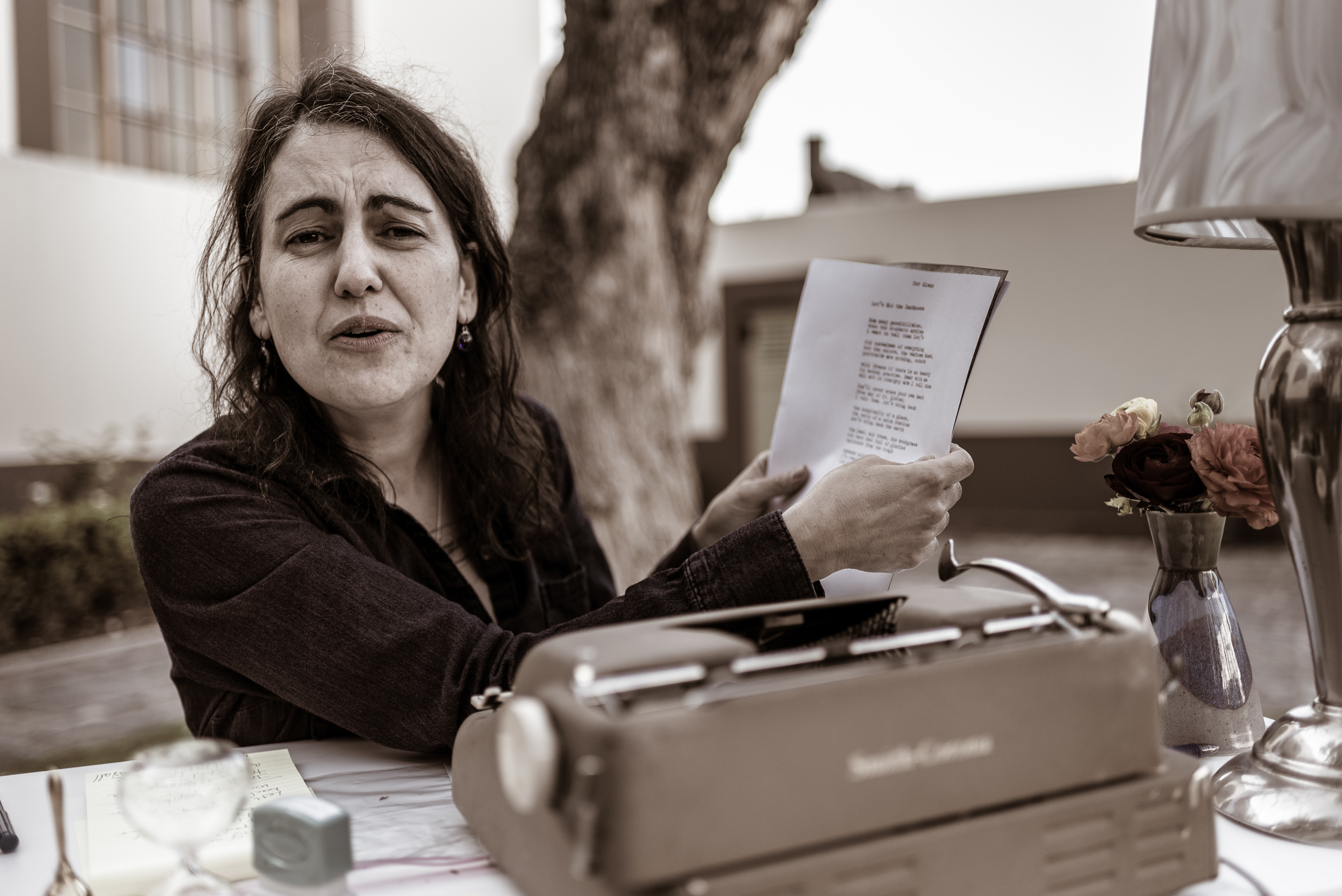 "Poet Lory Bedikian at a typewriter on a table on the grass of Union Station's North Patio on the occasion of ""The Poet Is In"", and event celebrating National Poetry Month."