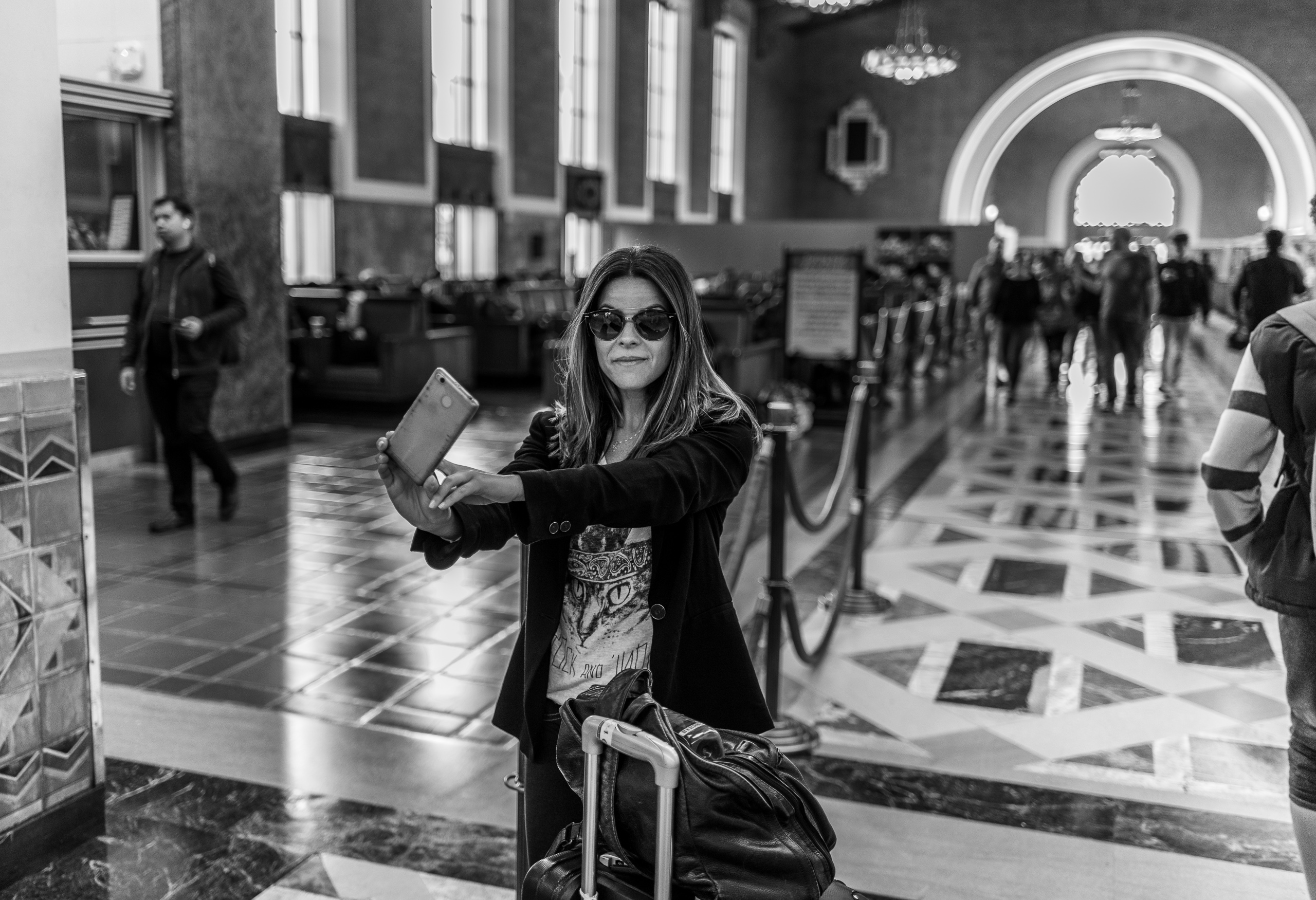 a woman in sunglasses, a black jacket, and a cat t-shirt stands with her luggage and her cell phone extended in front of her to take a selfie with the arches of Union Station's main terminal receding in the distance behind her