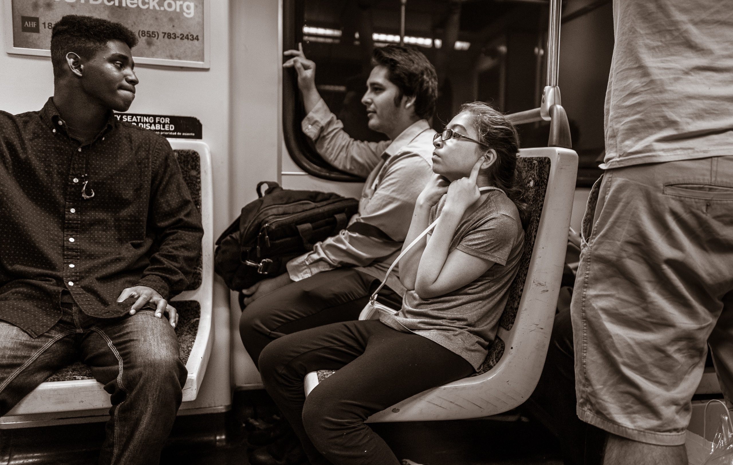 a young girl on a Metro Red Line train car plugs her ears with her fingers