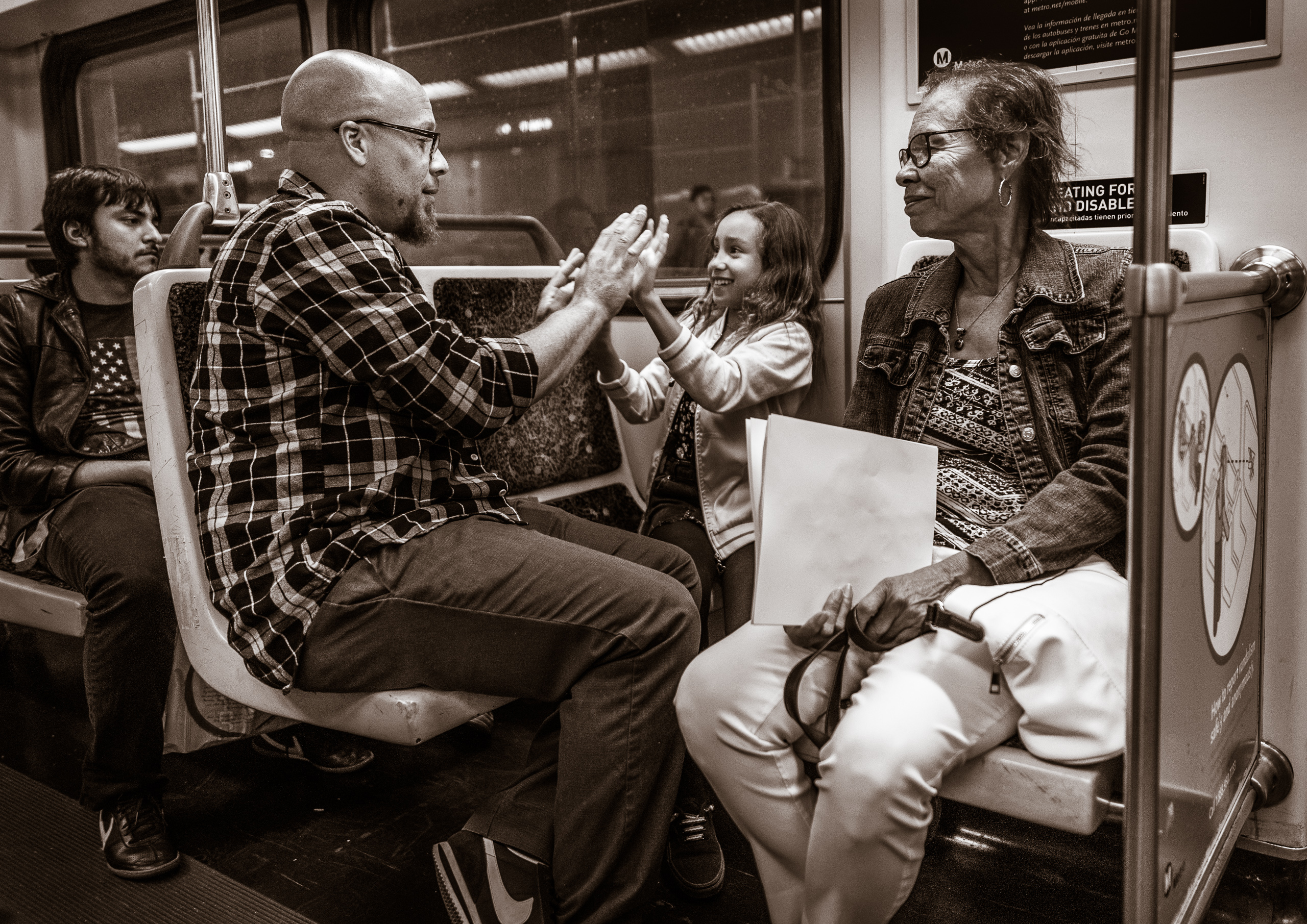 a father and daughter play Patty Cake on a Metro Red Line car as grandma watches and smiles