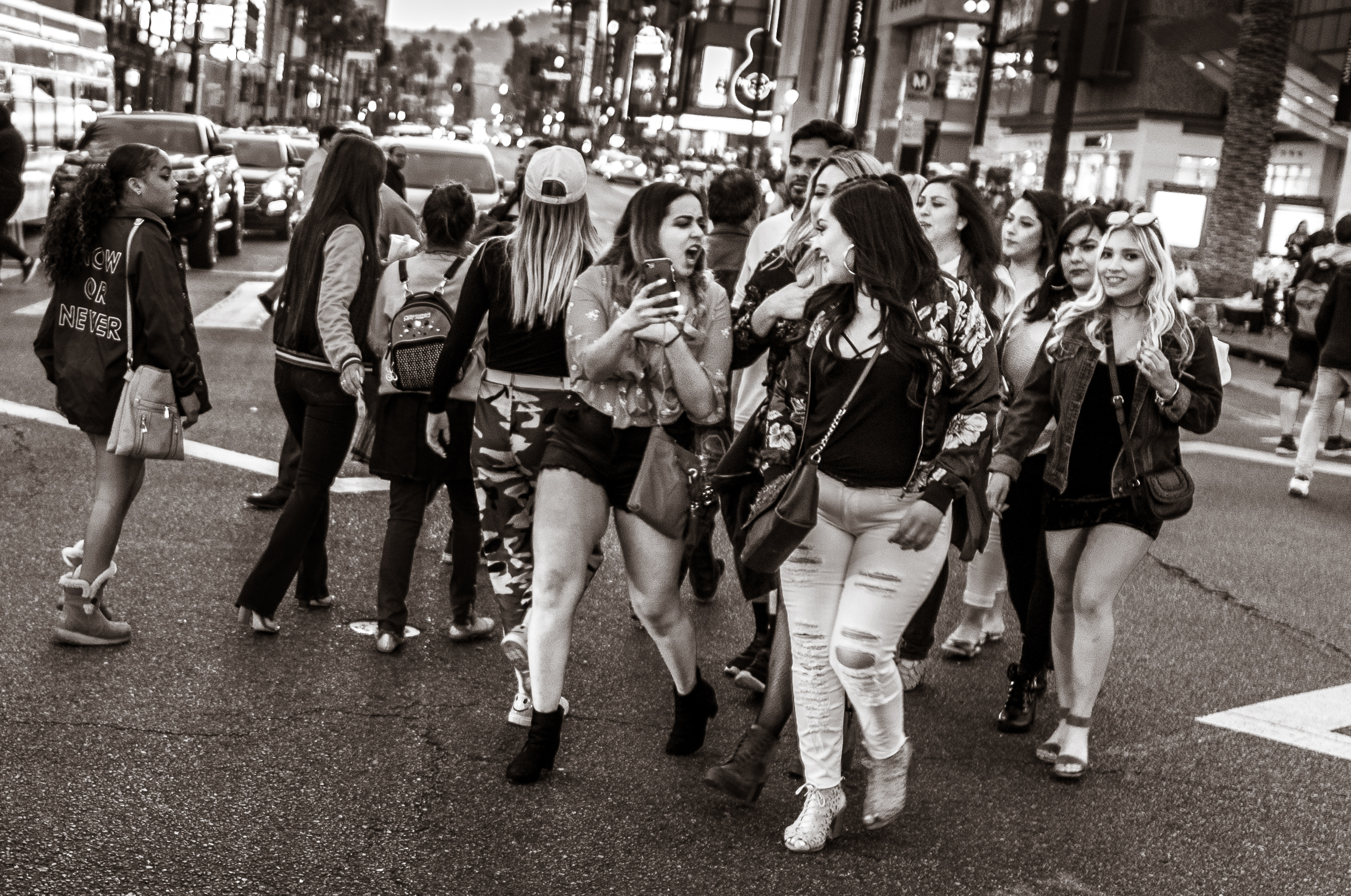 a group of women cross the street at the 4-way crossing at Hollywood & Highland in Hollywood, Los Angeles, CA. One person points at something on her cell phone and screams something to her friend