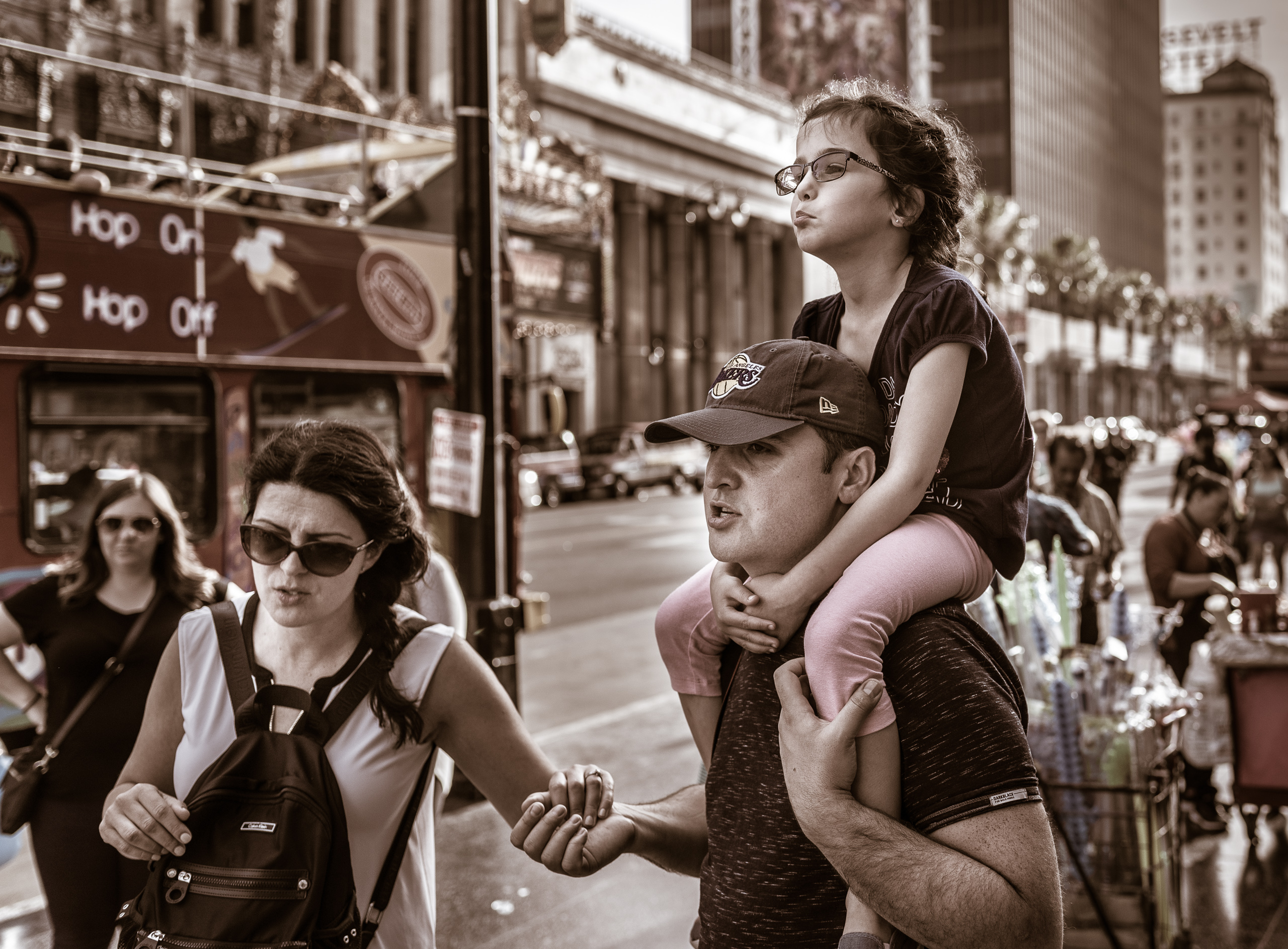 "a young girl rides on her dad's shoulders. Her dad holds hands with her mom. All 3 walk down Hollywood Blvd and pass a tour bus that says on the side, ""Hop on, hop off"""