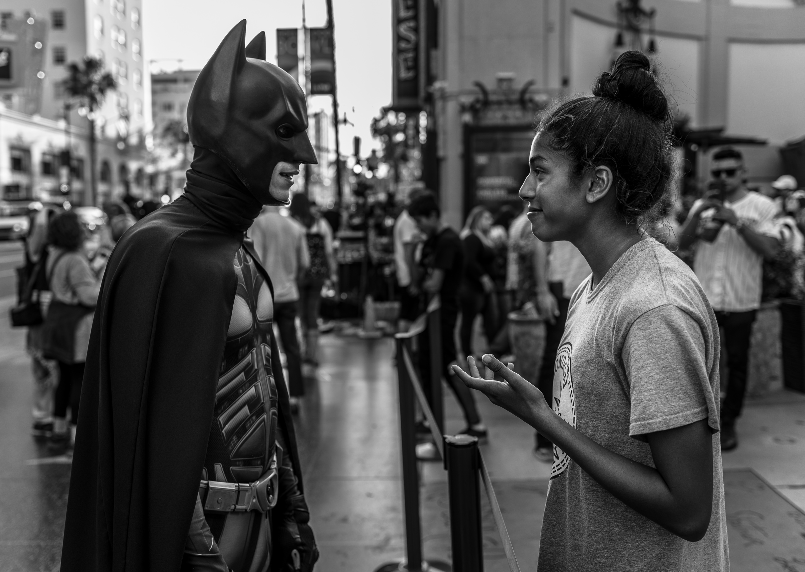a young woman has an engaging conversation with a guy in a Batman costume on Hollywood Blvd.