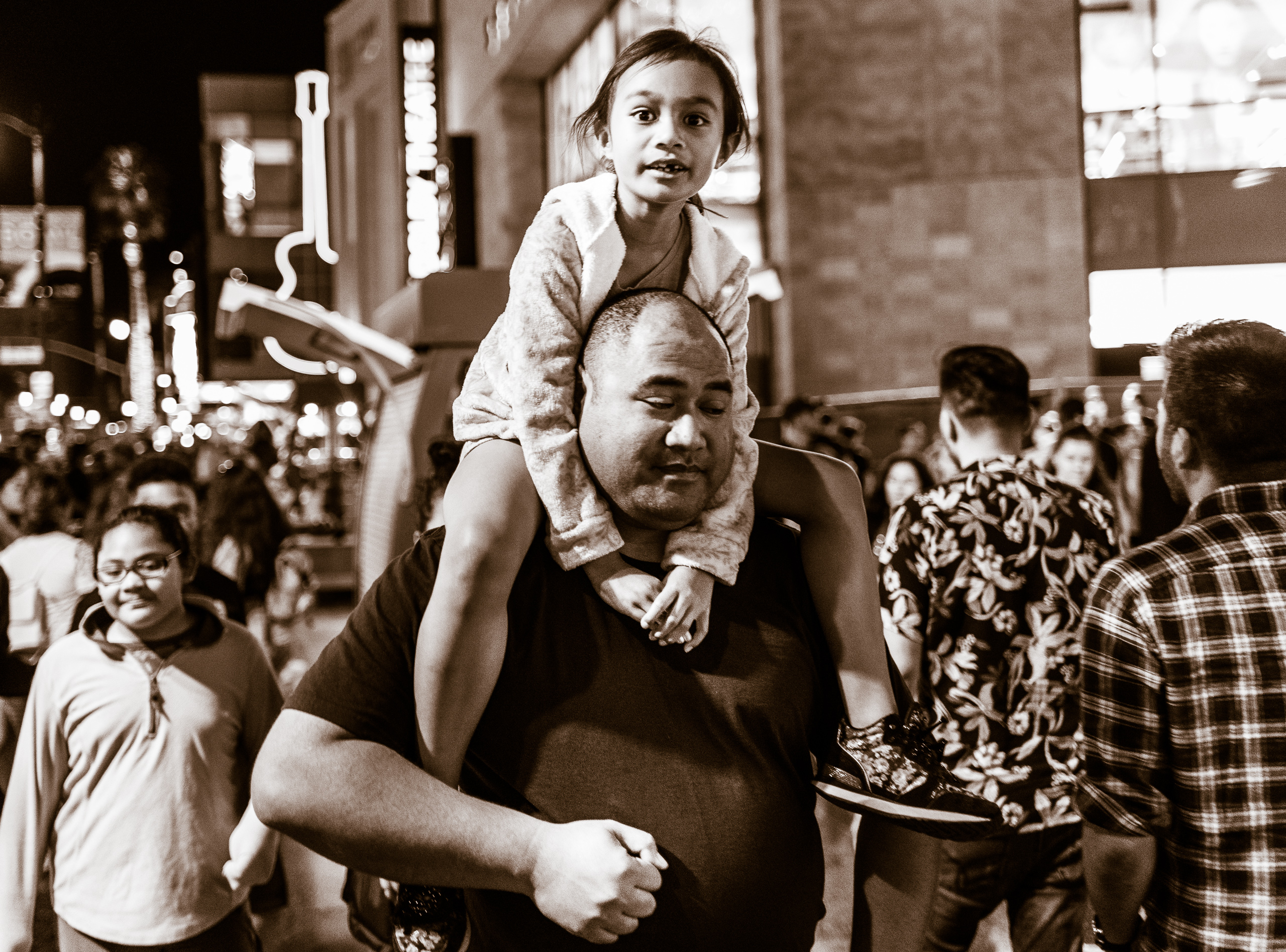 a tiny young girl rides on the shoulders of her big father