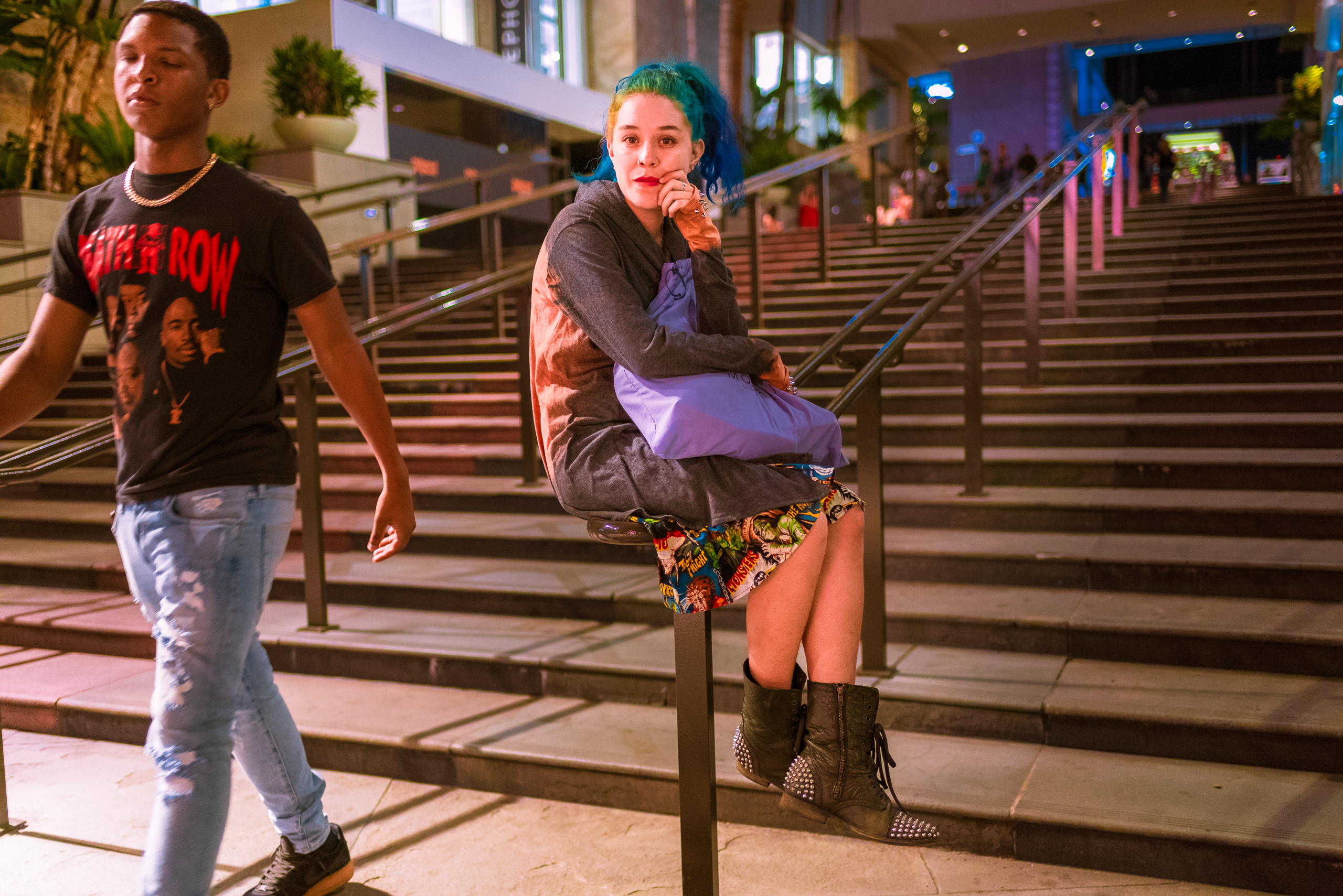 "a young woman sits on the handrail at the wide entrance stairs to the Hollywood & Highland shopping center. She wears a dress that, among other things, says ""Monsters"" on it."