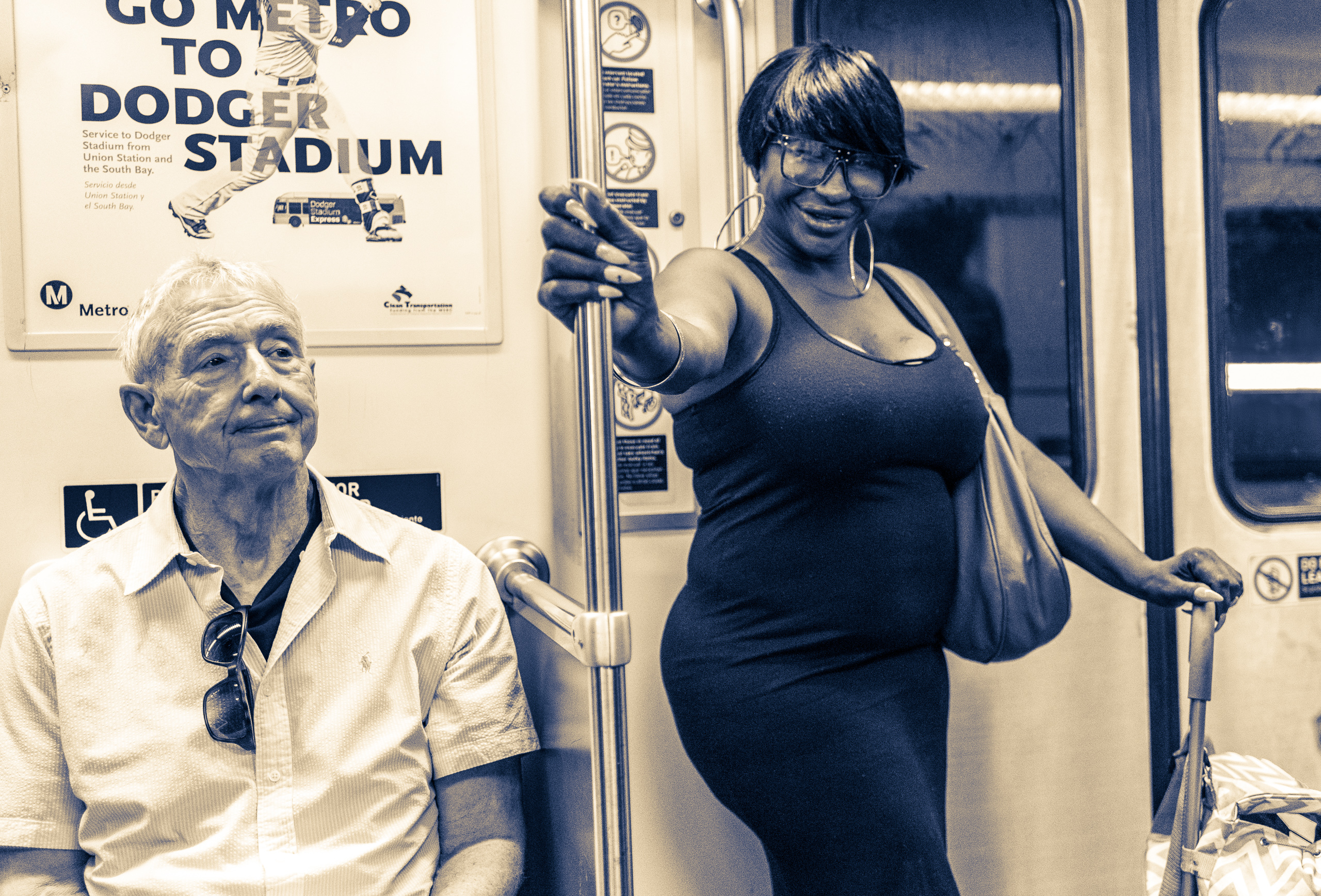 on a Metro Red Line train car from Hollywood to Downtown LA, a Black woman in a black dress stands next to a White man in a white shirt