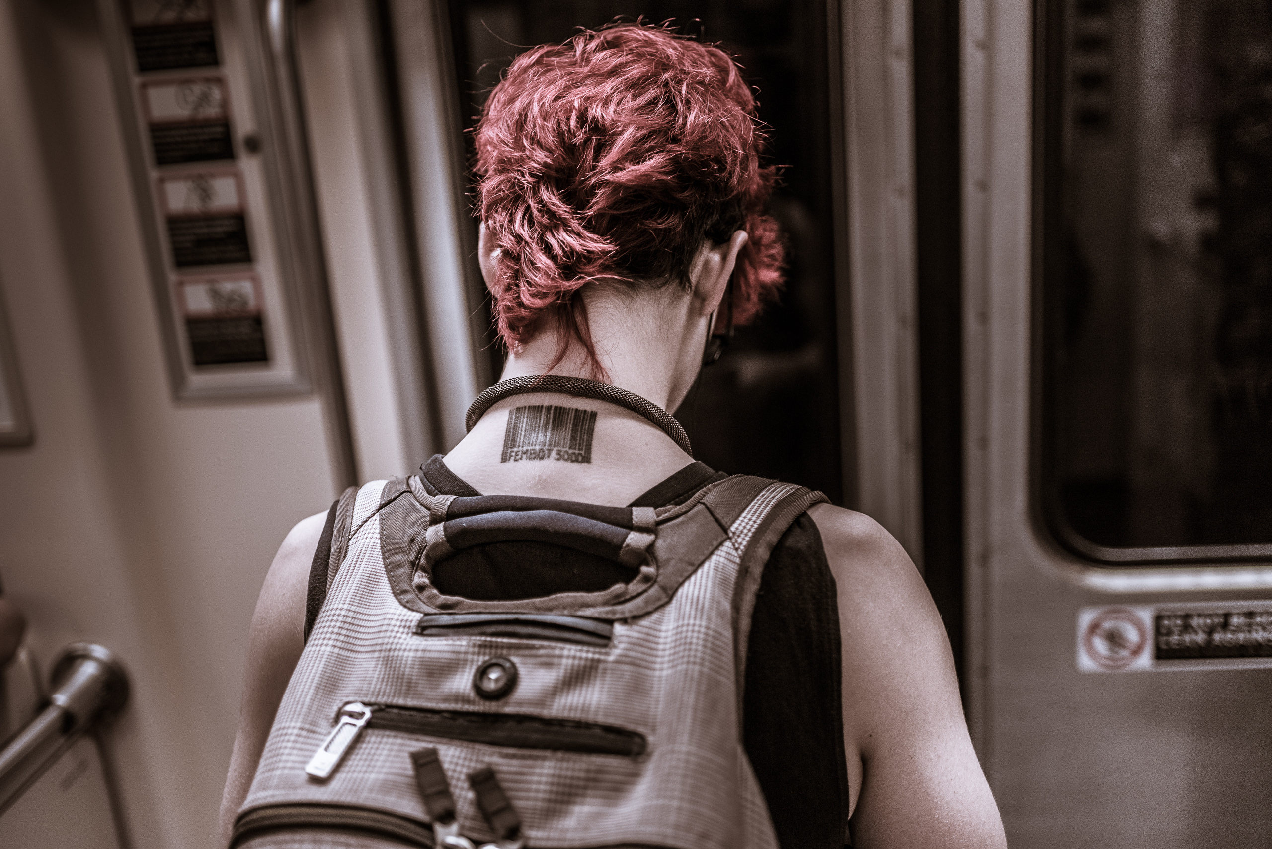 "a woman with short, red hair stands in an LA Metro Red Line train car. On the back of her neck is a tattoo bar code with the text ""Fembot 3000"""