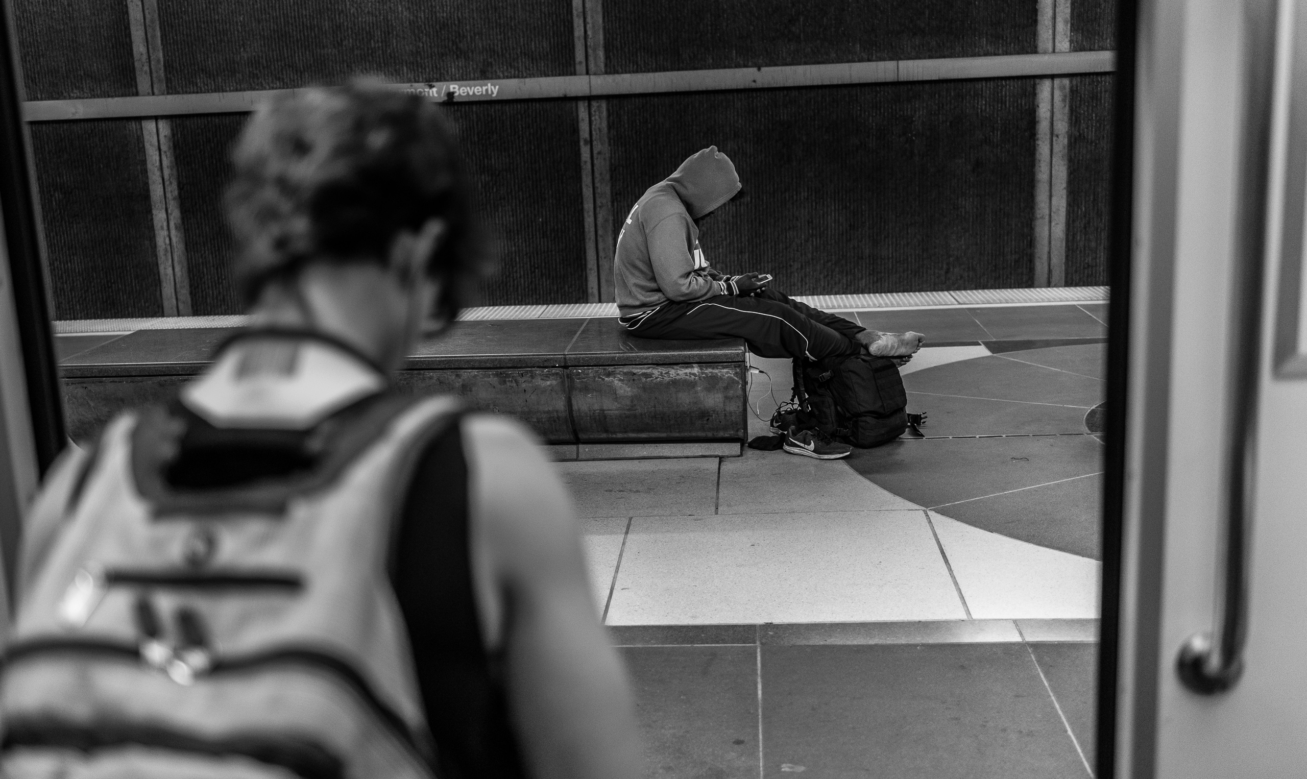 Photograph from a Metro Red LIne train car looking out to the Platform at Vermont/Beverly station. A guy sits on a concrete bench with his shoes off, his feet propped up on a bag, and his phone in hand and also charging with a cable