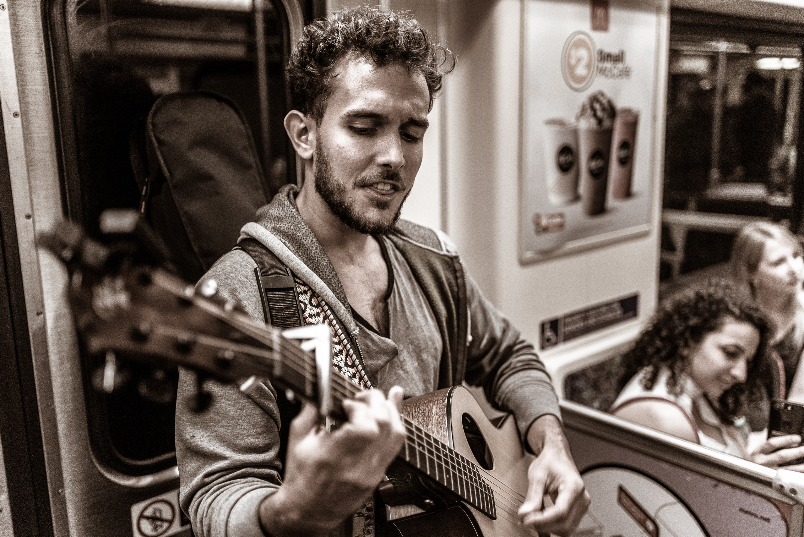 a guy plays guitar and sings on a Metro Red Line car heading to Hollywood