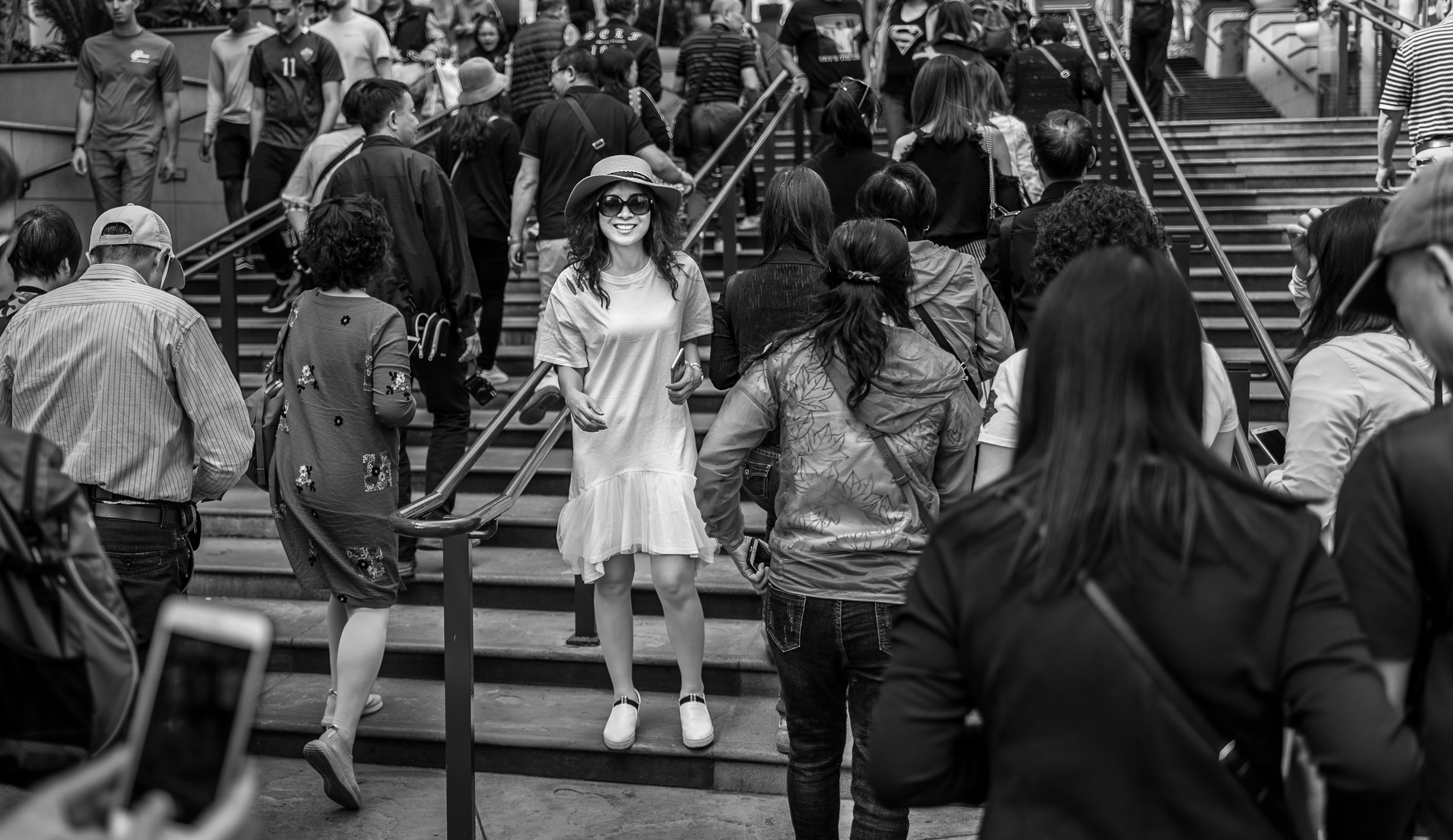 a thick, ocean of people in dark clothing head up the stairs, and away from the camera, at the entrance to the Hollywood & Highland center. In the middle one woman, in a bright, white dress, turns and faces the camera