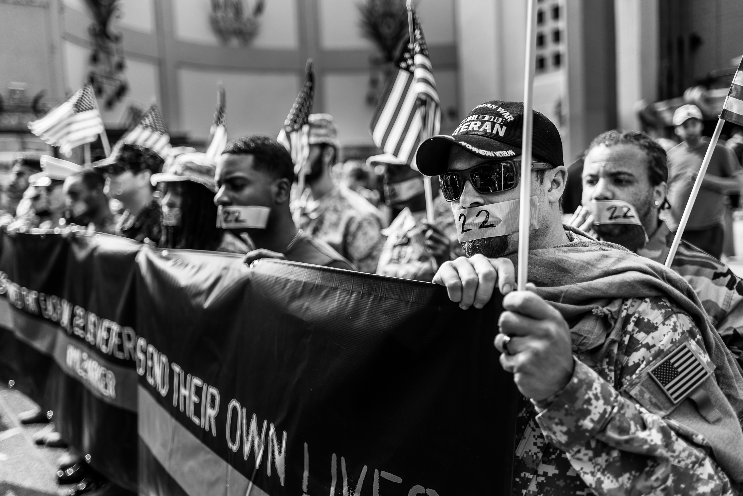 """over a dozen Unites States veterans from different branches stand dressed in their respective uniforms and with their mouths covered with duct tape bearing the number""""22"""" and together they hold a long banner reading """"It's estimated that each day, 22 US Veterans end their own lives"""". They stand in front of the Chinese Theater on Hollywood Blvd."""
