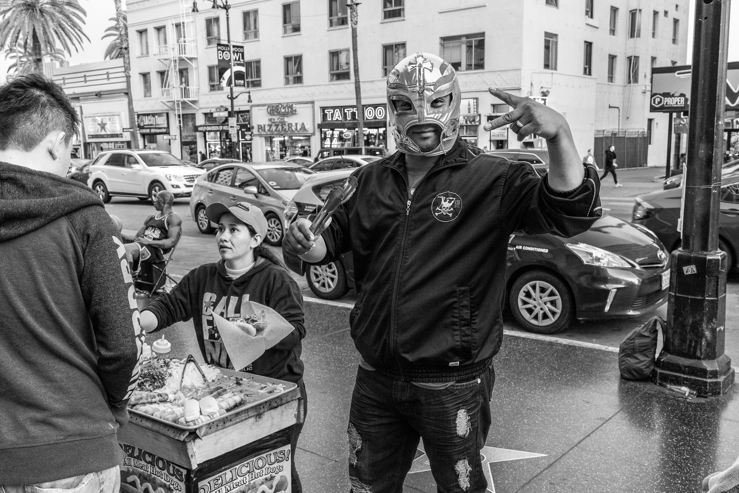 a hot dog vendor on Hollywood Blvd holds grill tongs and wears a Lucha Libre mask