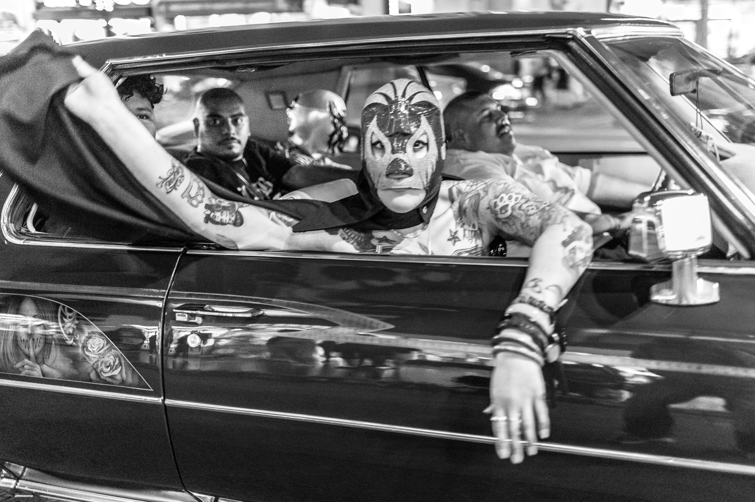 a guy in a Lucha Libre mask sticks his head out the car window and holds his cape in the breeze as his car moves down Hollywood Blvd.
