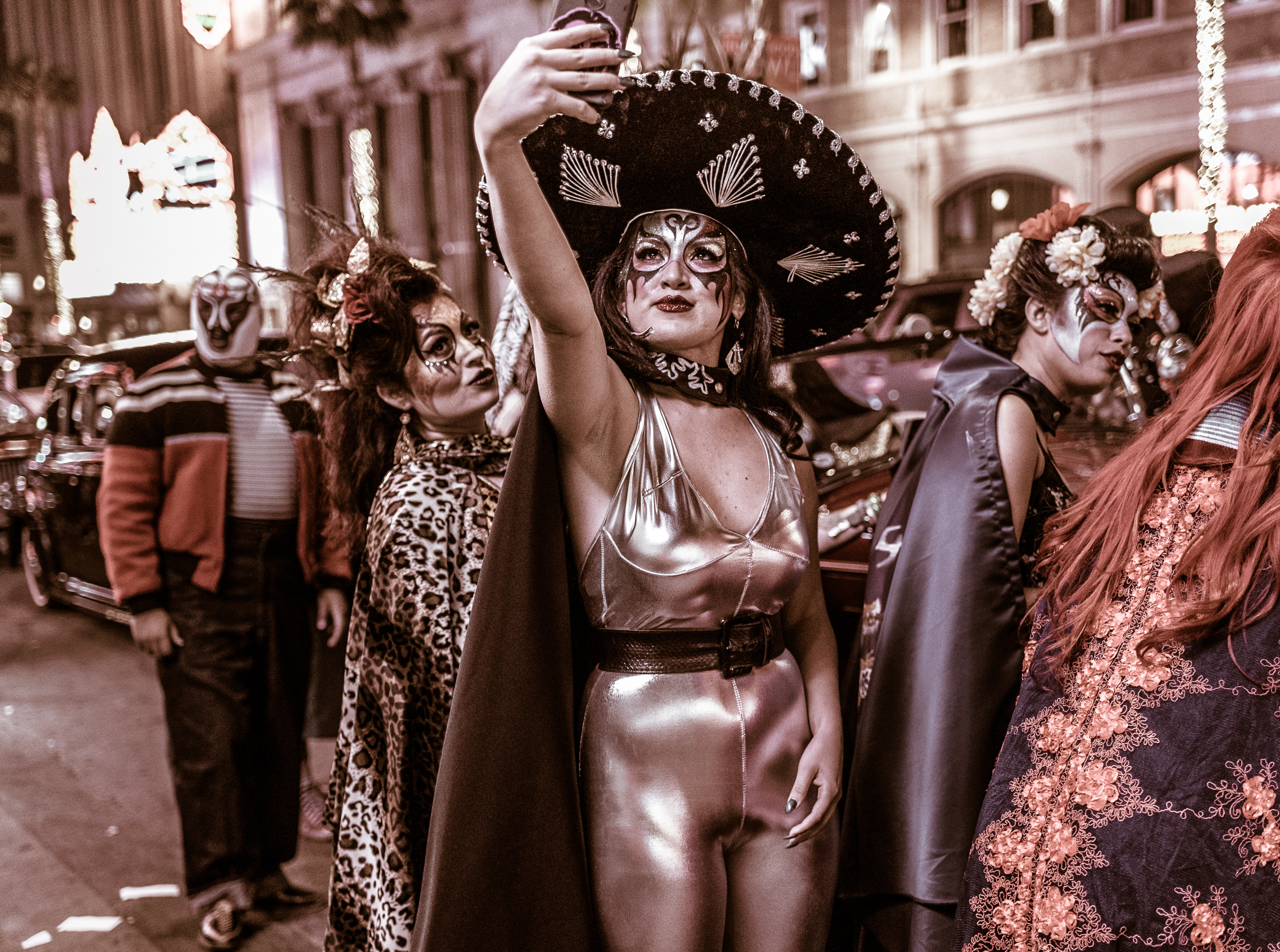 a woman in Lucha Libre facepaint, a large sombrero, a shiny silver catsuit, and a black cape, holds a cell phone triumphantly up to the heavens and points it back at herself standing on Hollywood Blvd to take a selfie