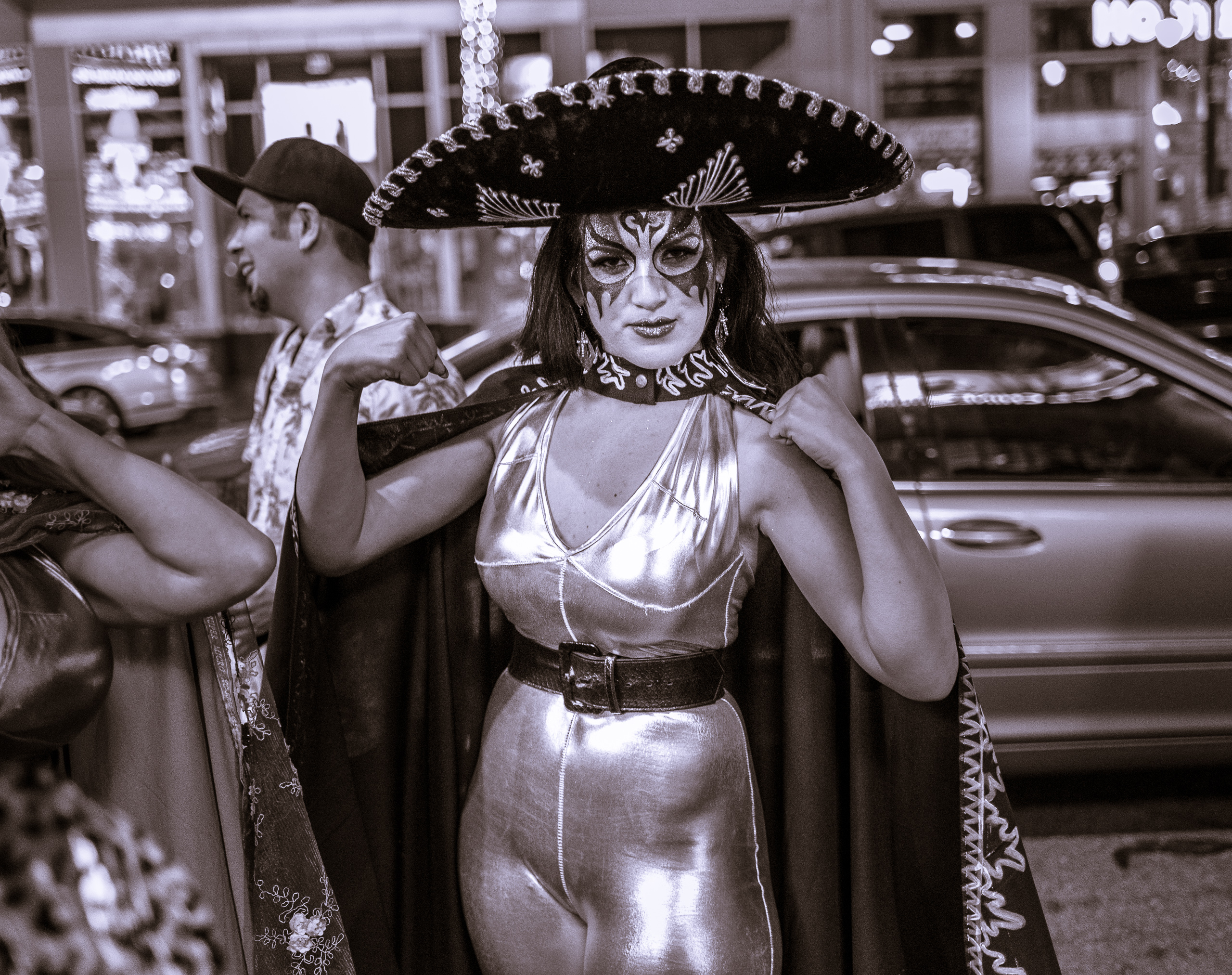a female lucha libre wrestler in a mylar catsuit with a painted face and a huge sombrero flexes her muscles on Hollywood Blvd