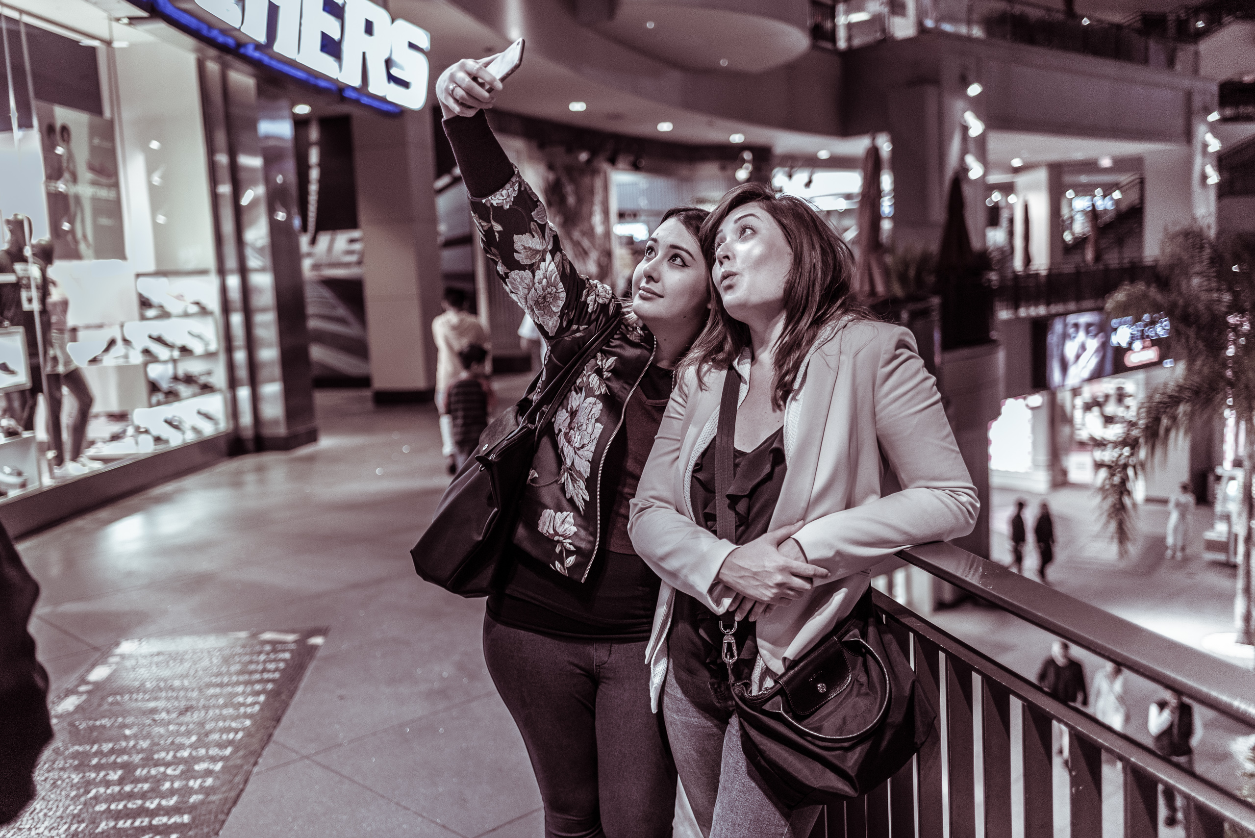 two women stand on a second level deck at the Hollywood & Highland center. In front and to the side of them is a large, bright window and sign from a Sketchers store. One of them holds a cell phone up in the air and they both smile for the high-angle selfie that includes people walking around on ground level below them.
