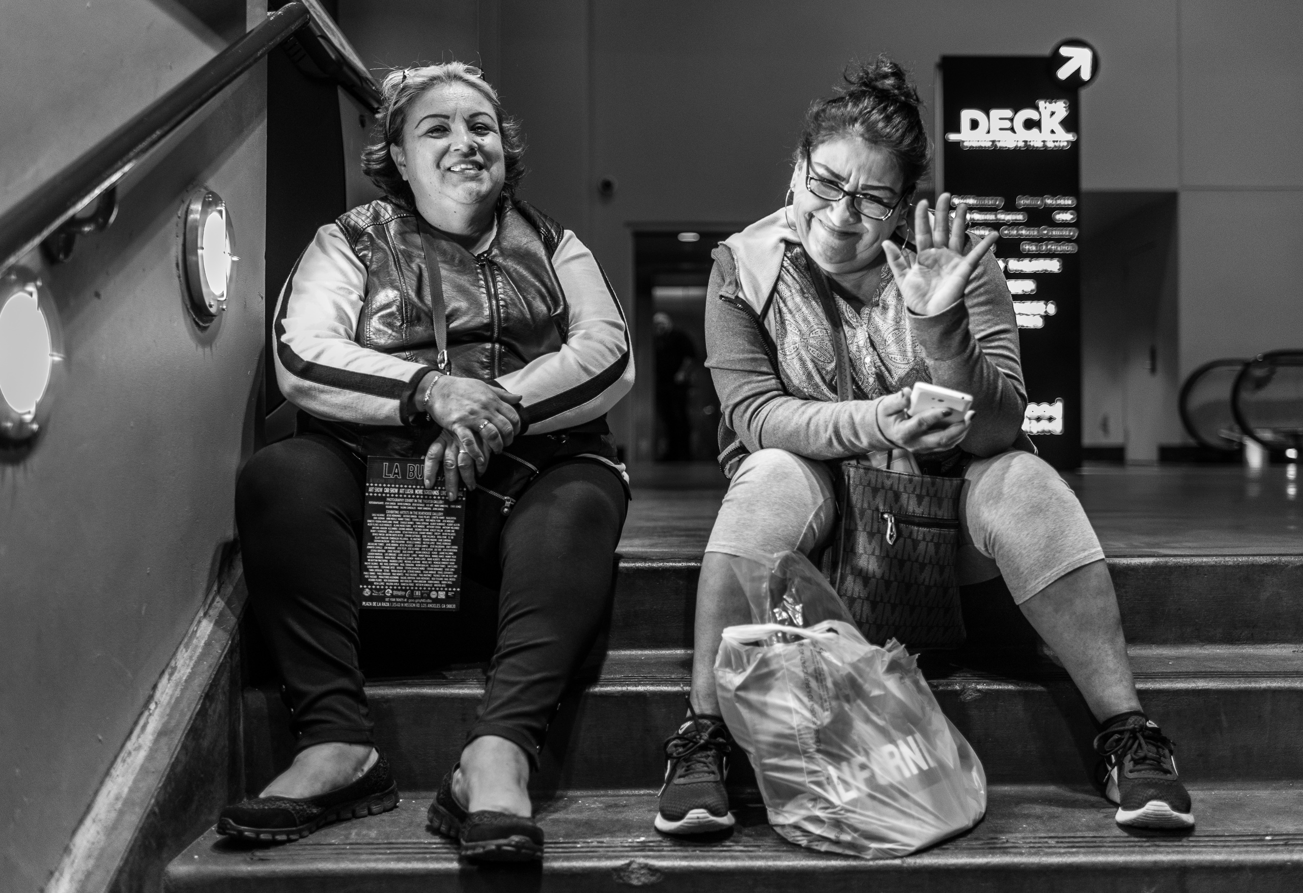 two women sit on the stairs next to the ticket booth at the TCL Chinese Theater in Hollywood, California
