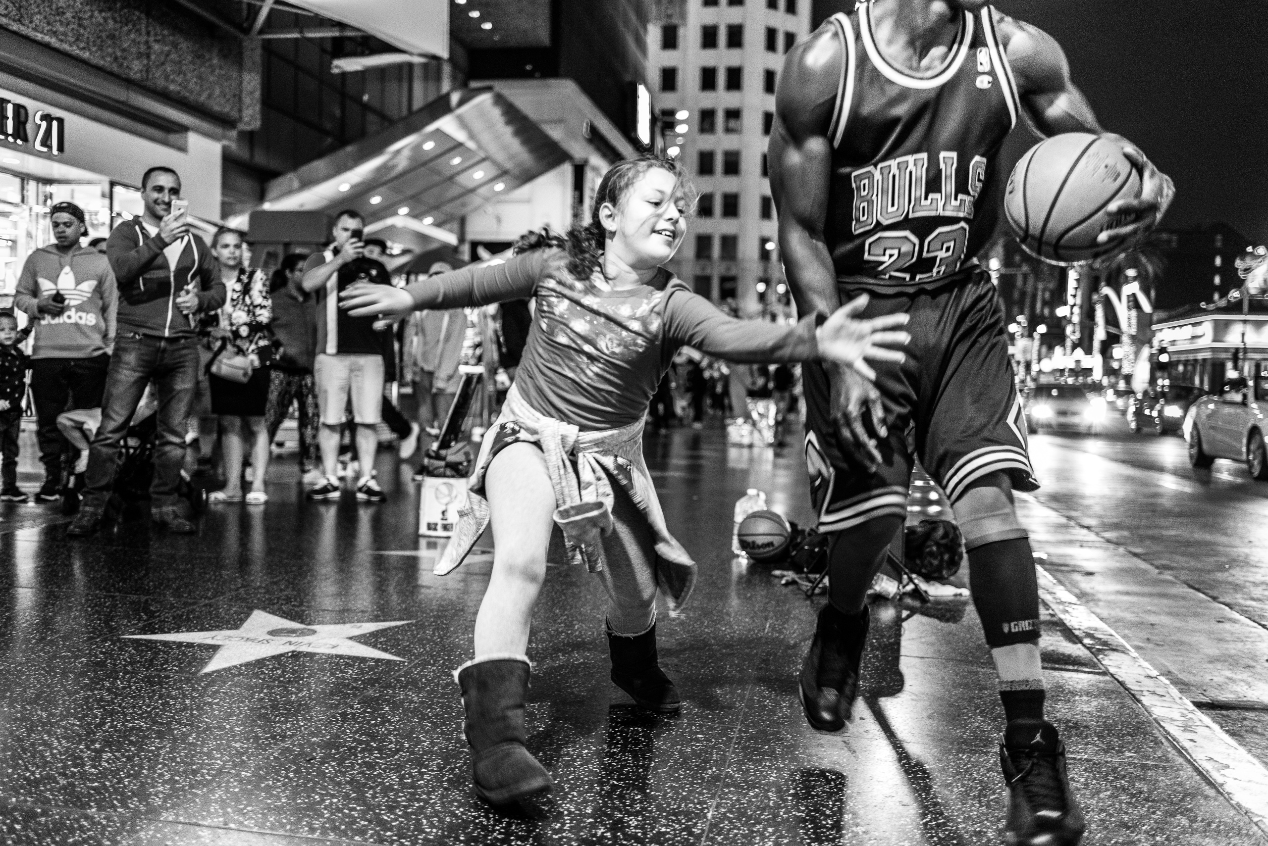 "a young girl tries, in vain, to steal a basketball from a ""Michael Jordan"" character on Hollywood Blvd. Here dad and others watch and smile and video the competition with their cell phones."