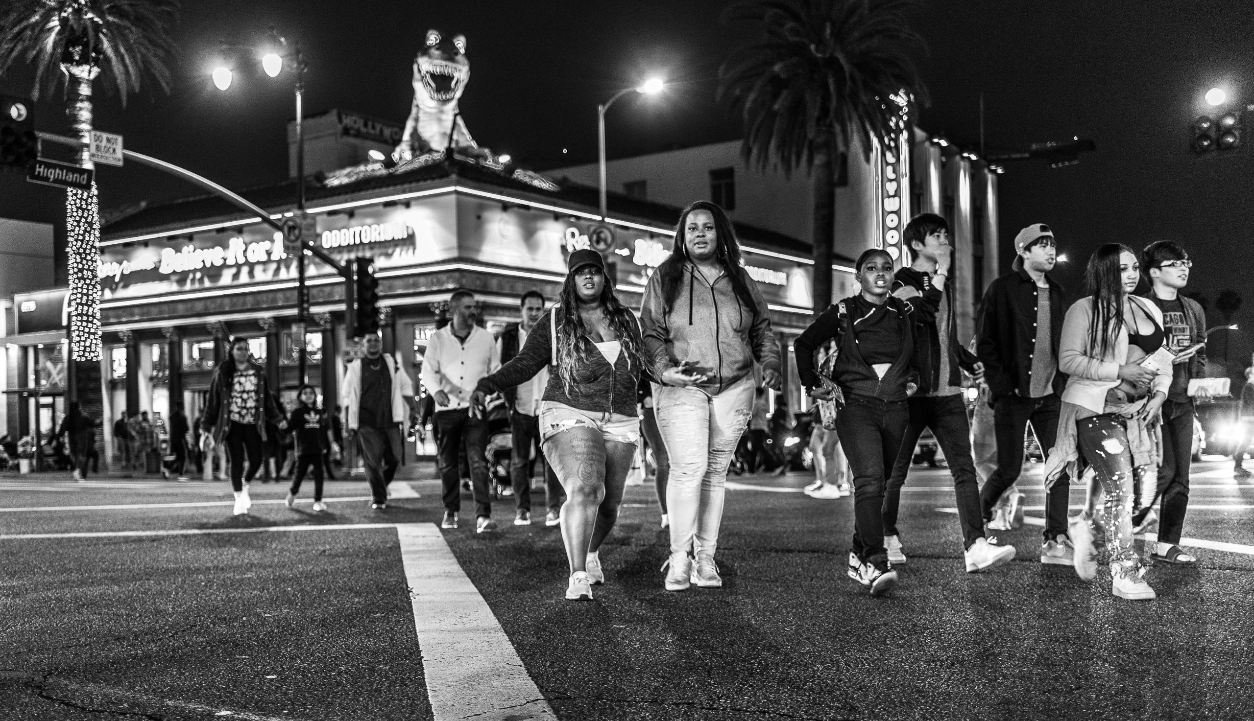 middle of the 4-way crossing at Hollywood Blvd & Highland Blvd. Camera is pointed southeast, and photographs a group of people diagonally crossing to the northwest corner of the intersection
