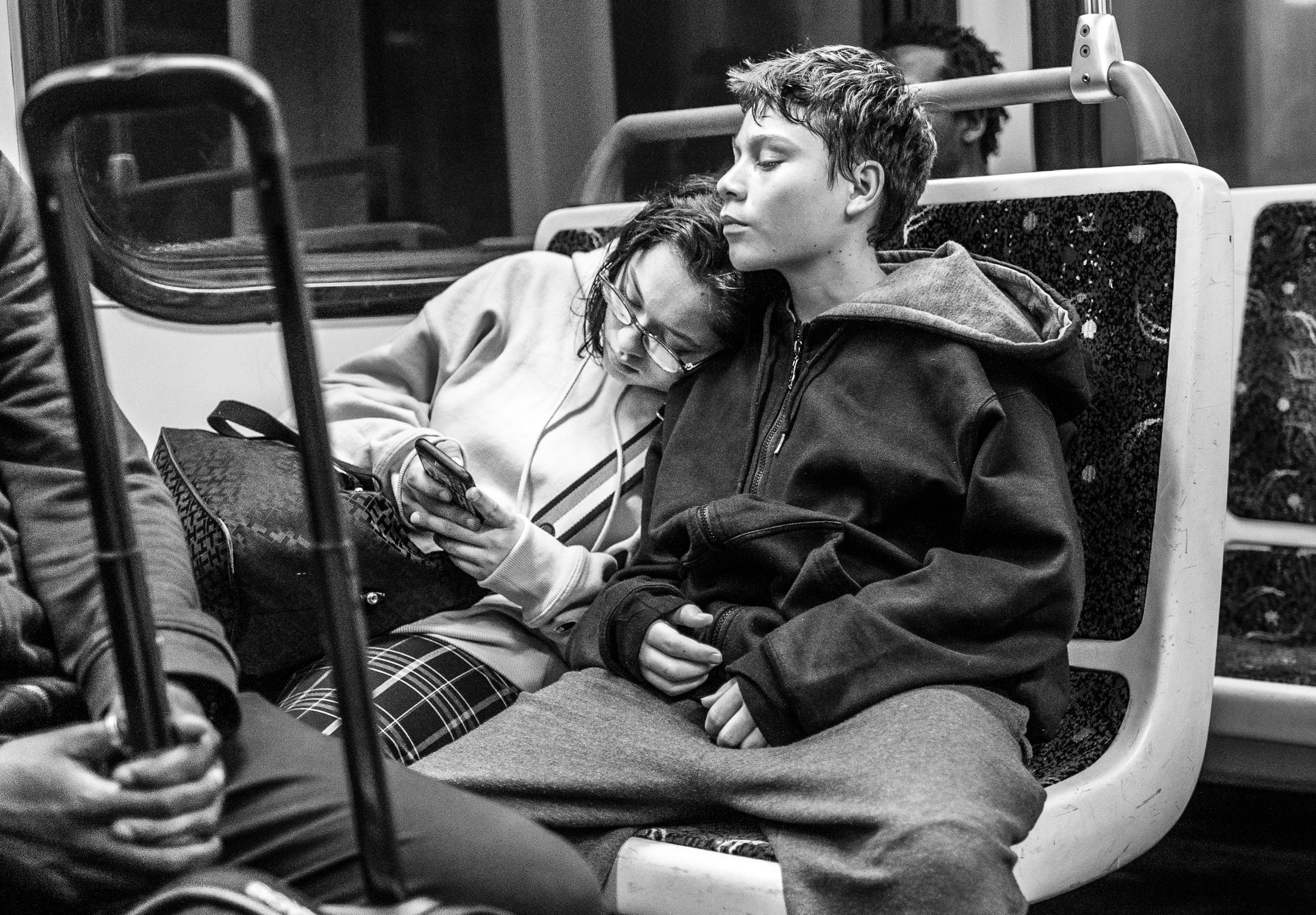 A girl rests her head on a guy's shoulder and looks at her phone. He rests his head on her head. They both look so very tired.