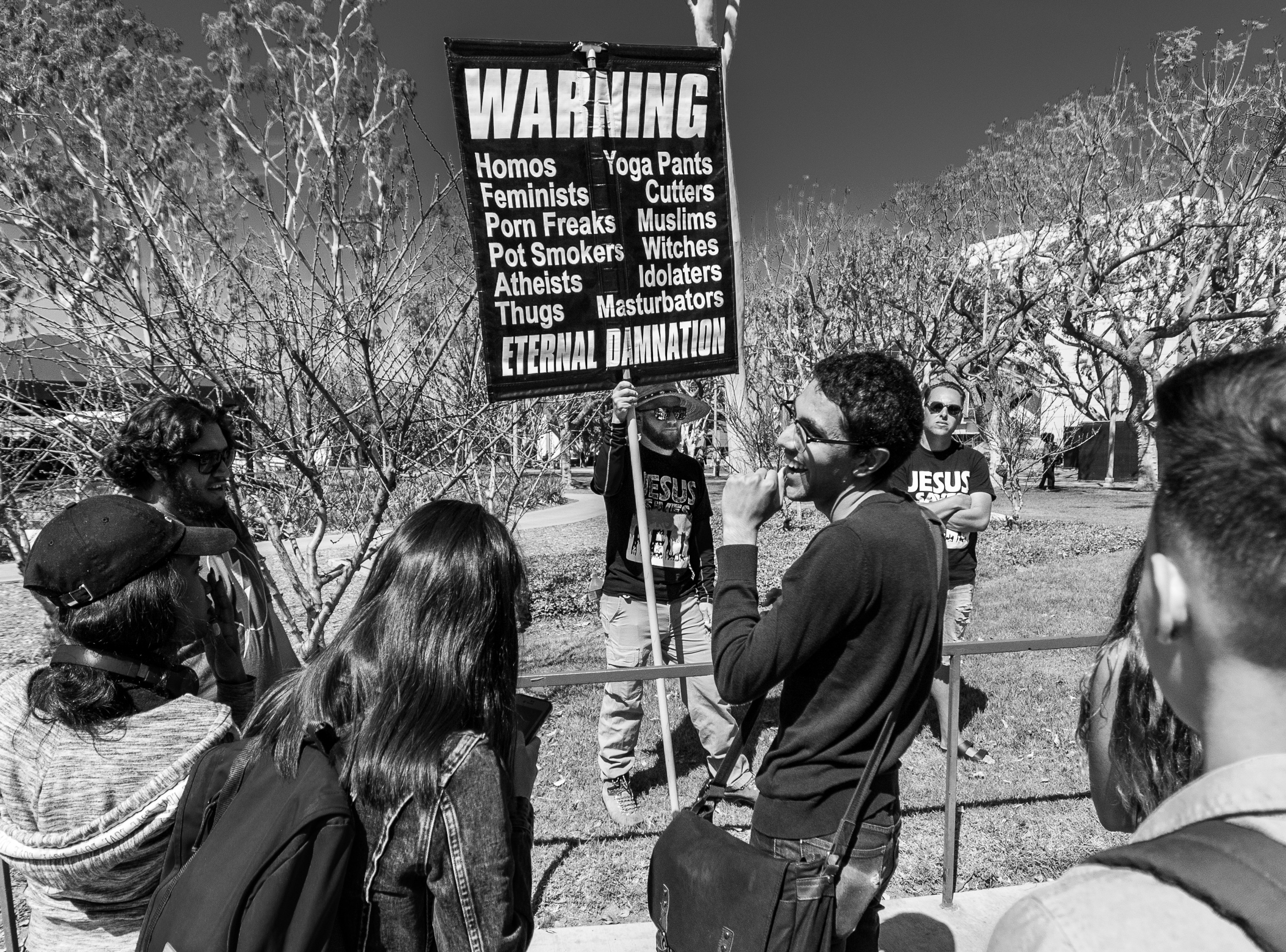 "a preacher with a large banner reading ""Warning, Eternal Damnation"""