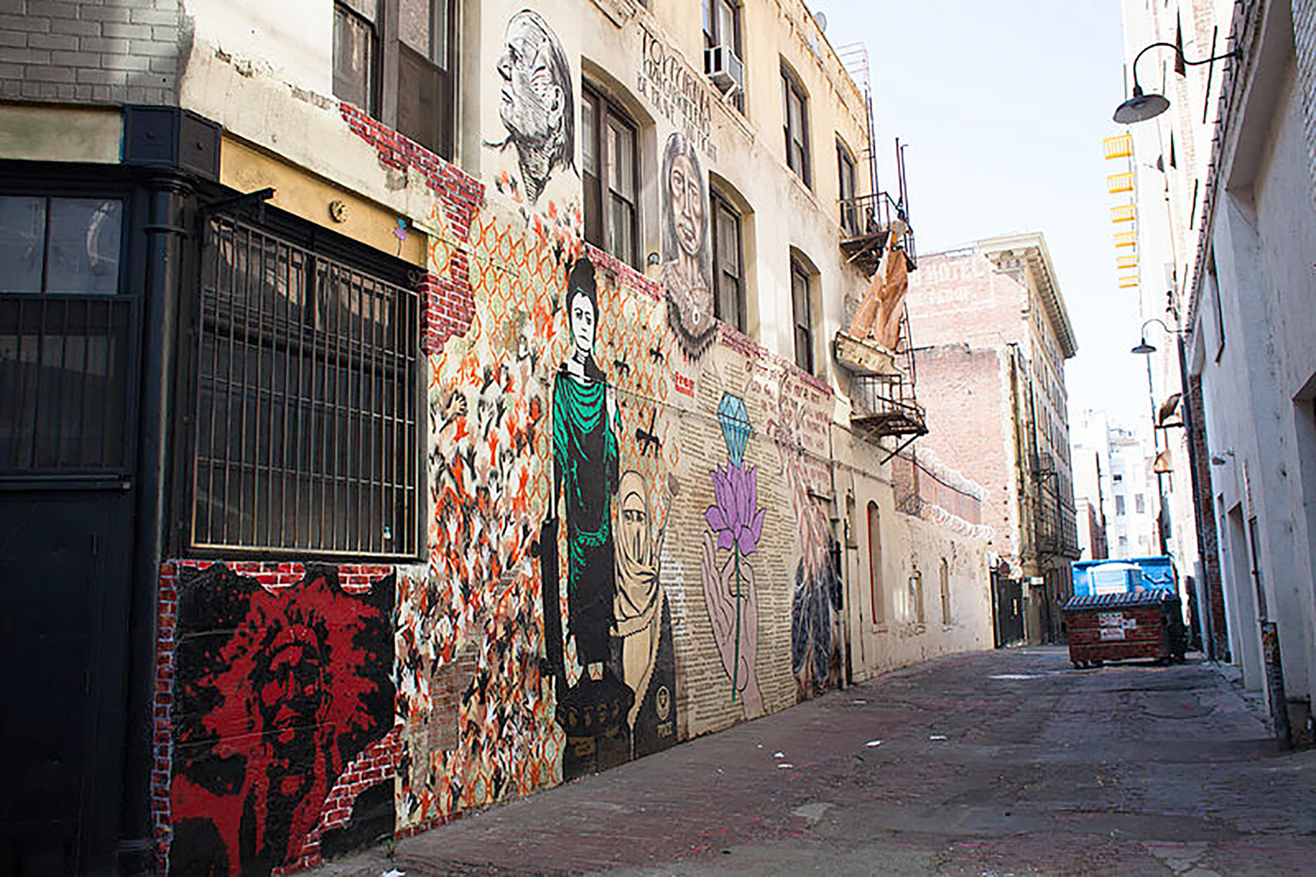 a view of Indian Alley in Downtown Los Angeles with murals and portraits painted on the backs of buildings along the alley