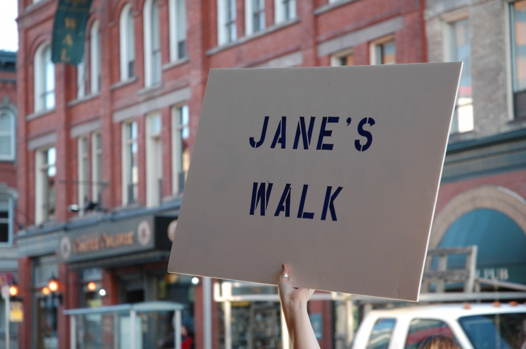 "a hand holding a ""Jane's Walk"" sign in the air"