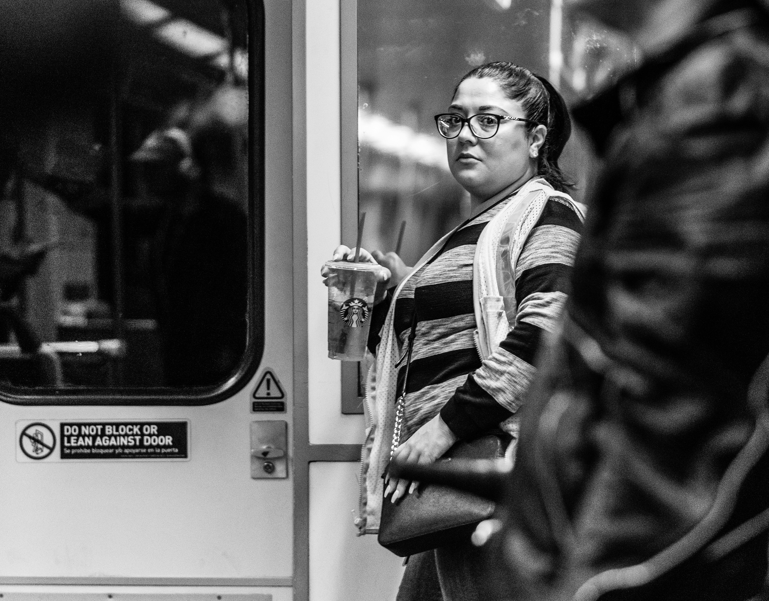 a woman stands at the end of a Metro Red Line Train Car and holds a Starbucks cup in her hand