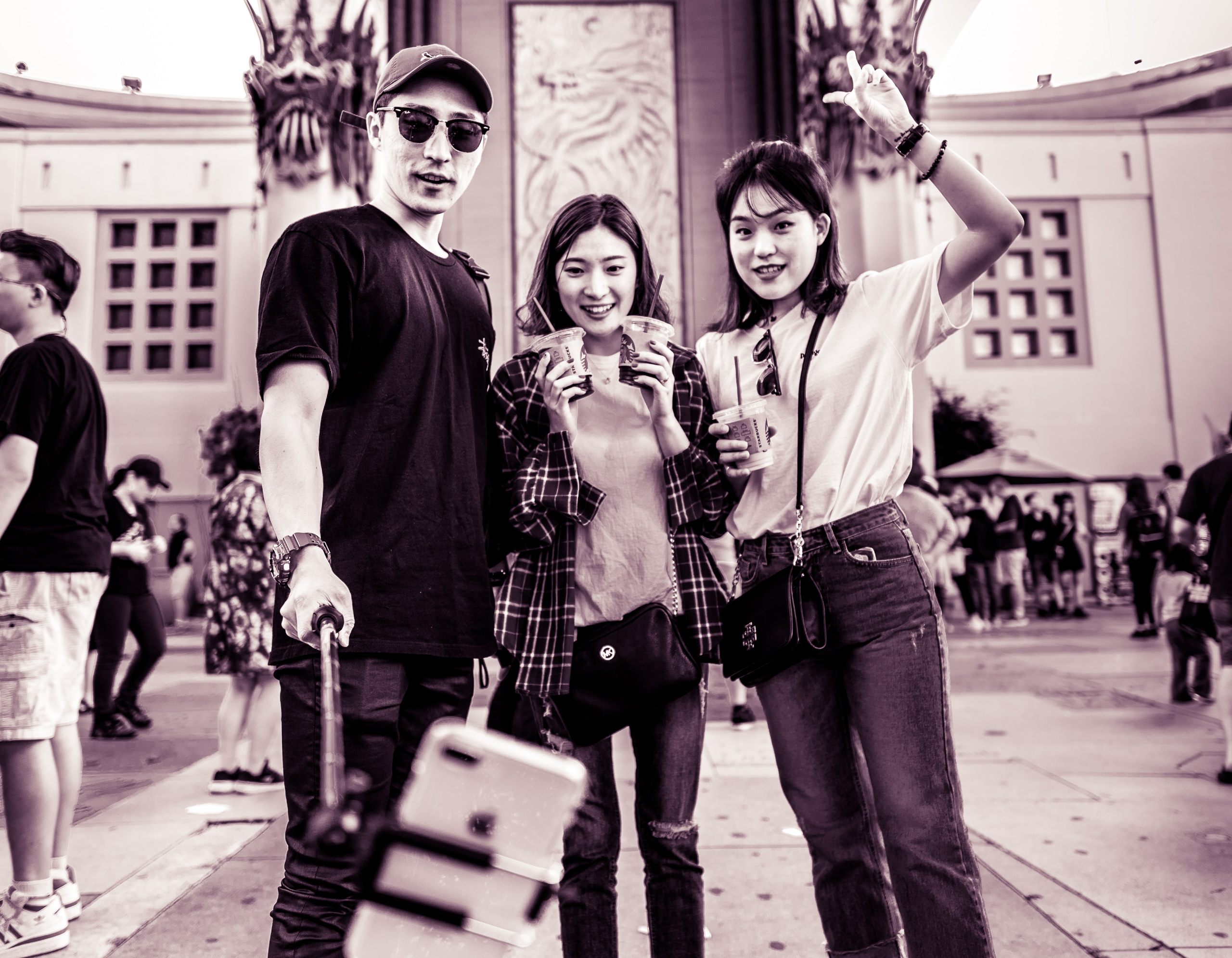 3 tourists stand in front of the Chinese Theater in Hollywood, CA and smile for a phone at the end of a long selfie stick