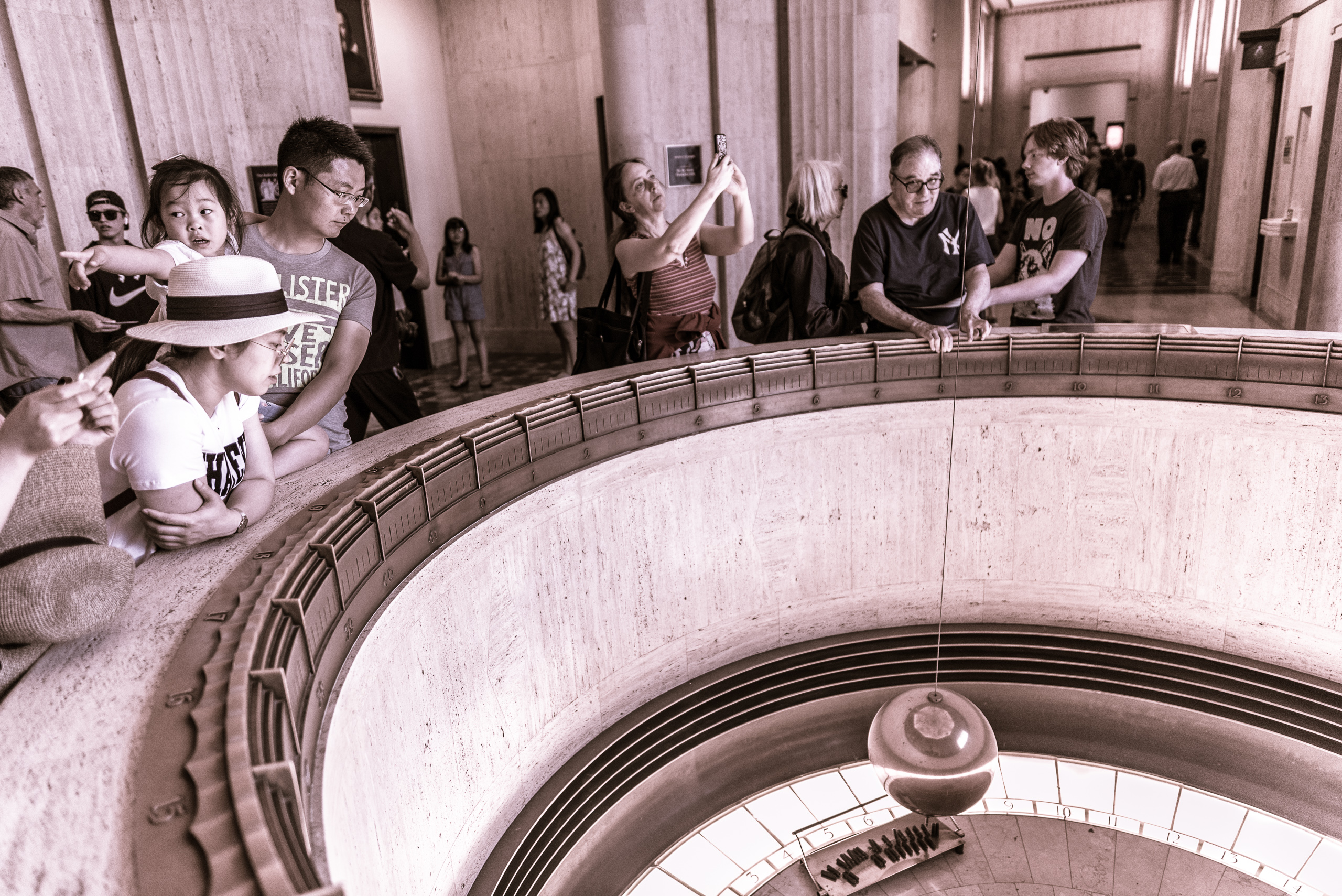 visitors at the Griffith Observatory in Griffith Park, Los Angeles, California look on as the large pendulum sways from side to side