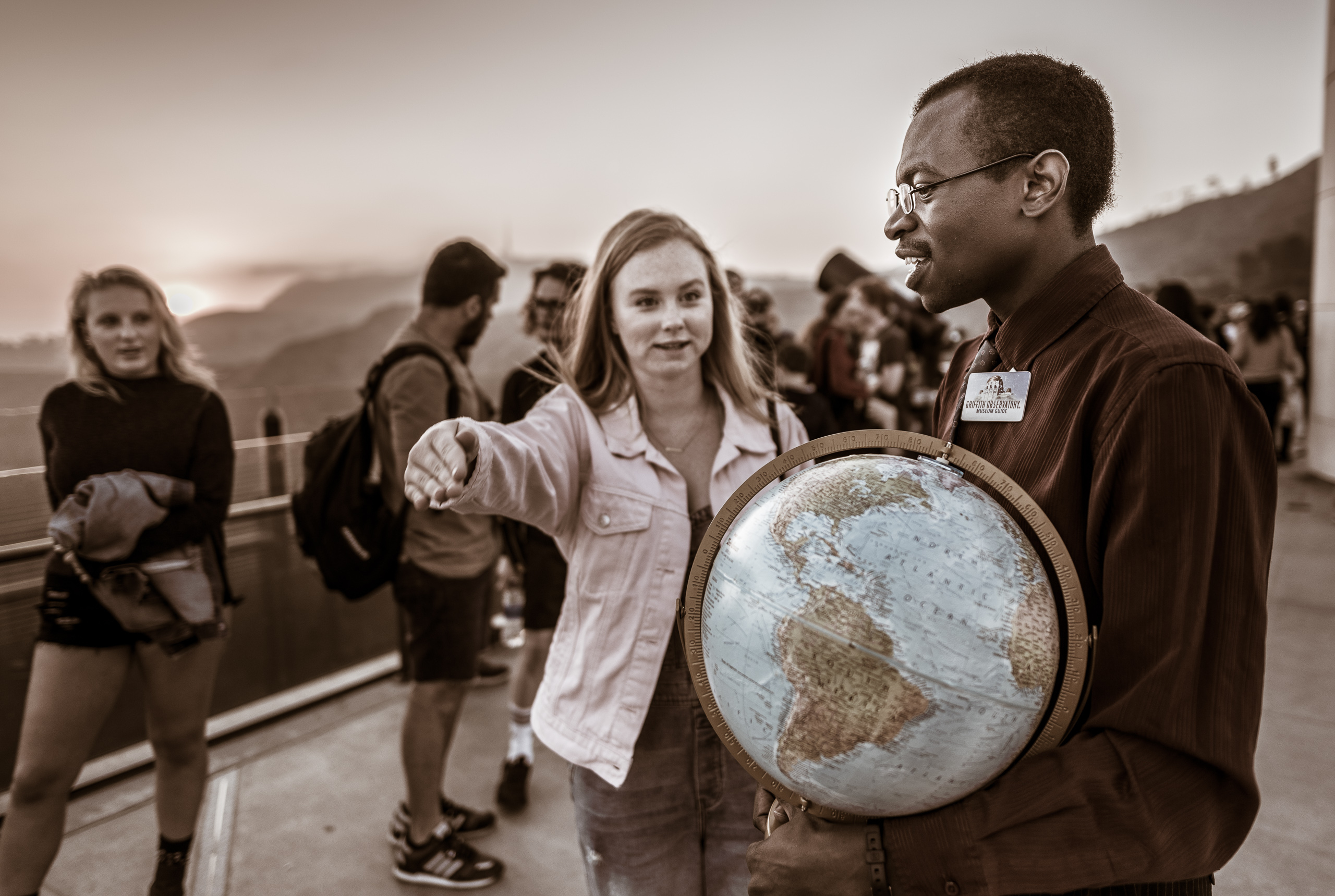A Griffith Observatory employee holds a globe in his hand as an observatory visitor asks him an astronomy question