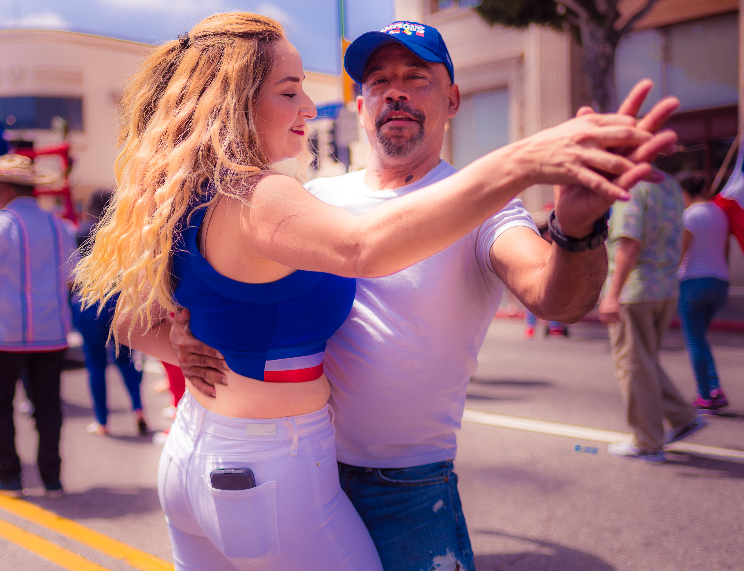 a woman in a blue crop top with a Dominican Republic flag-themed trim, and white pants, dances with a main in t-shirt and jeans on Hollywood Blve.