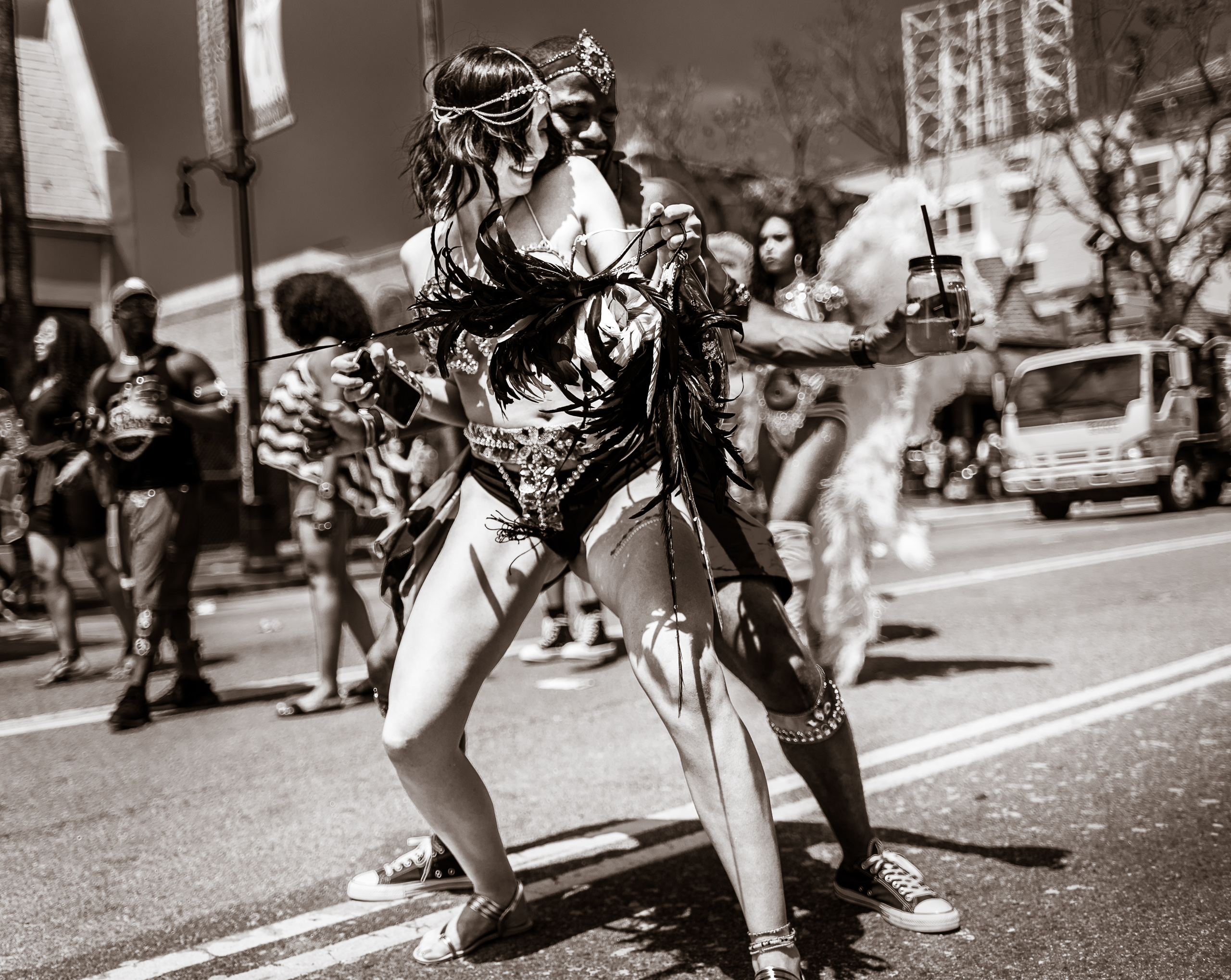 a girl in an elaborate costume and a guy behind her have fun dancing in the Hollywood Carnival Parade