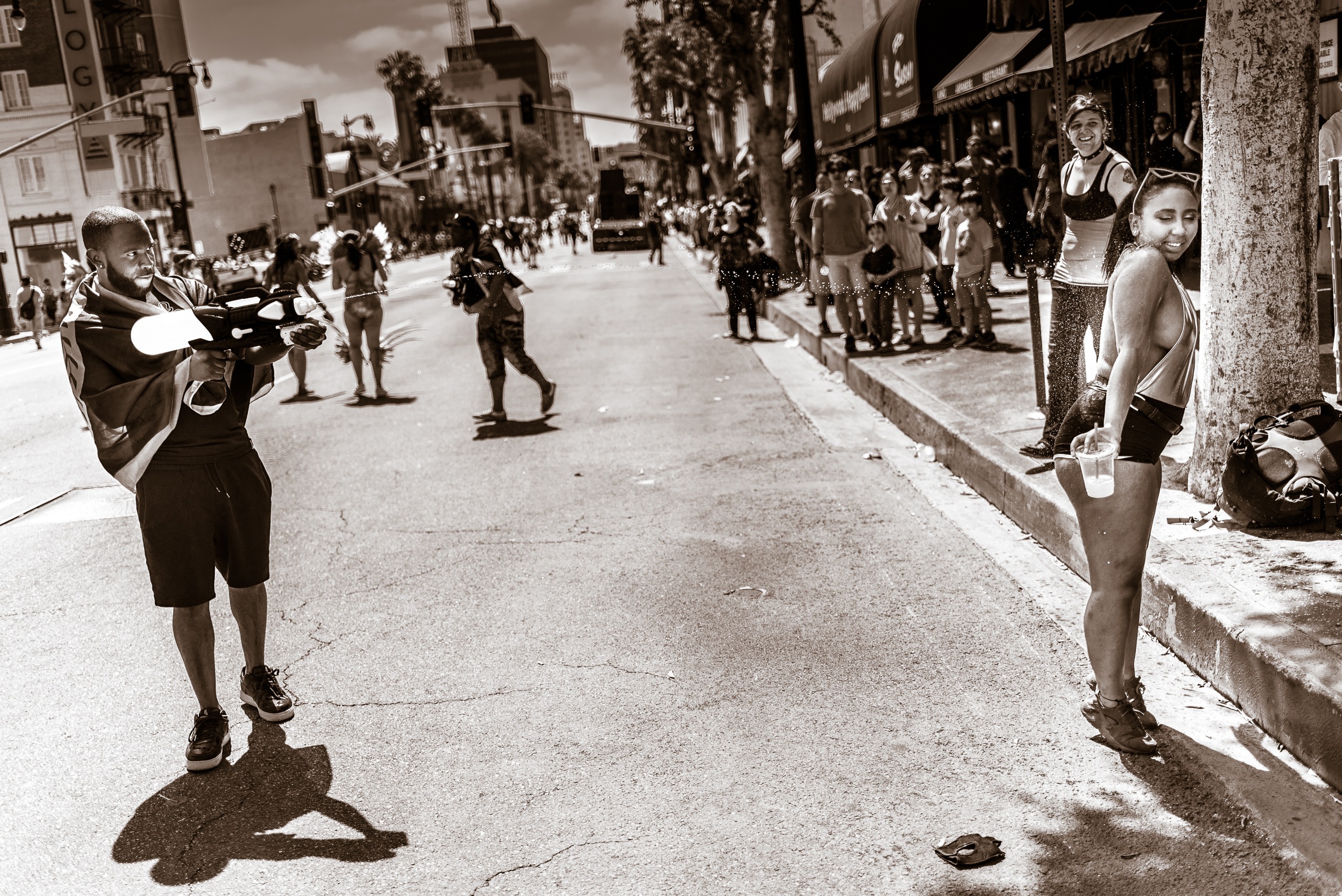 a guy stands in the middle of Hollywood Blvd and shoots a super soaker water stream at a dancer from the Hollywood Carnival Parade standing near the curb. She stands on her toes with her back to the water jet. Her eyes are closed and she seems to be enjoying the refreshing blast.
