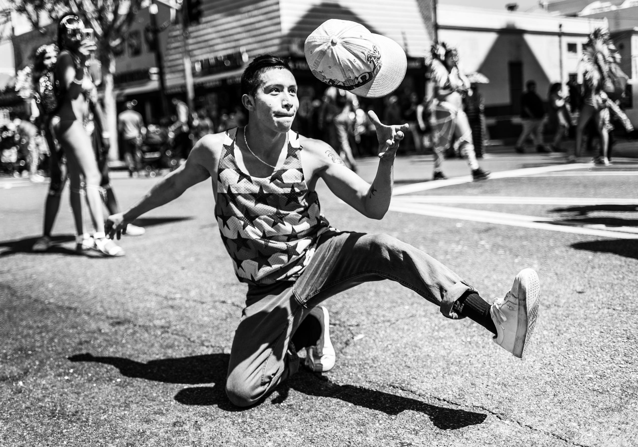Francisco Andres dancing on Hollywood Blvd during the Hollywood Carnival Parade. He has one leg up in the air, and has just thrown his hat under it. He's now catching the airborne hat with his hand