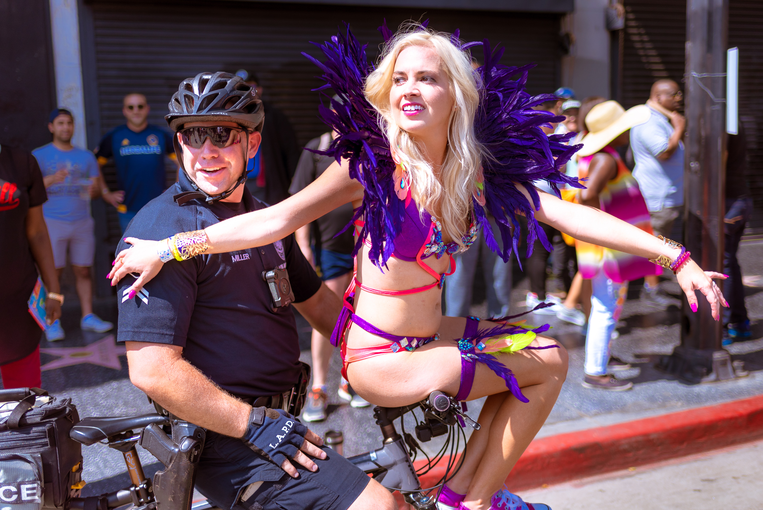 a dancer in the Hollywood Carnival Parade sits on the handlebars of an LAPD bicycle officer