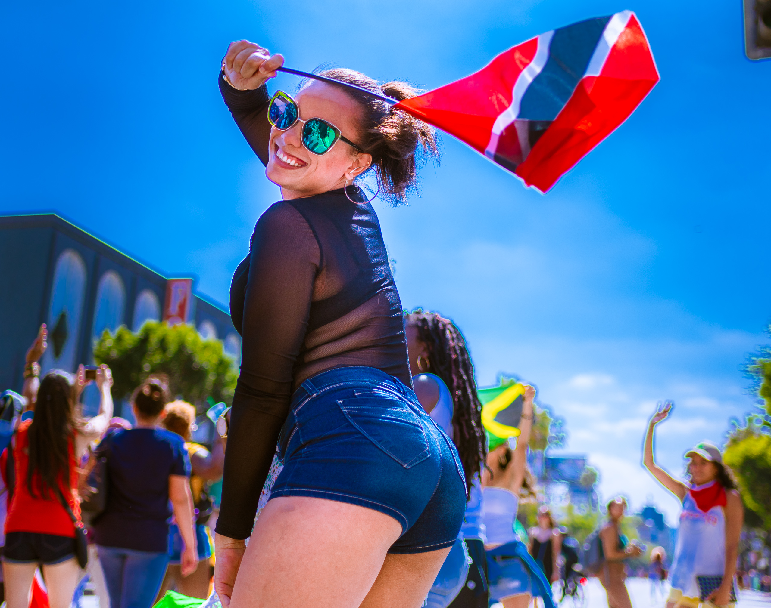 a woman in a black shirt and denim shorts joyously waves a Trinidad & Tobago red-white-black flag against a blue sky