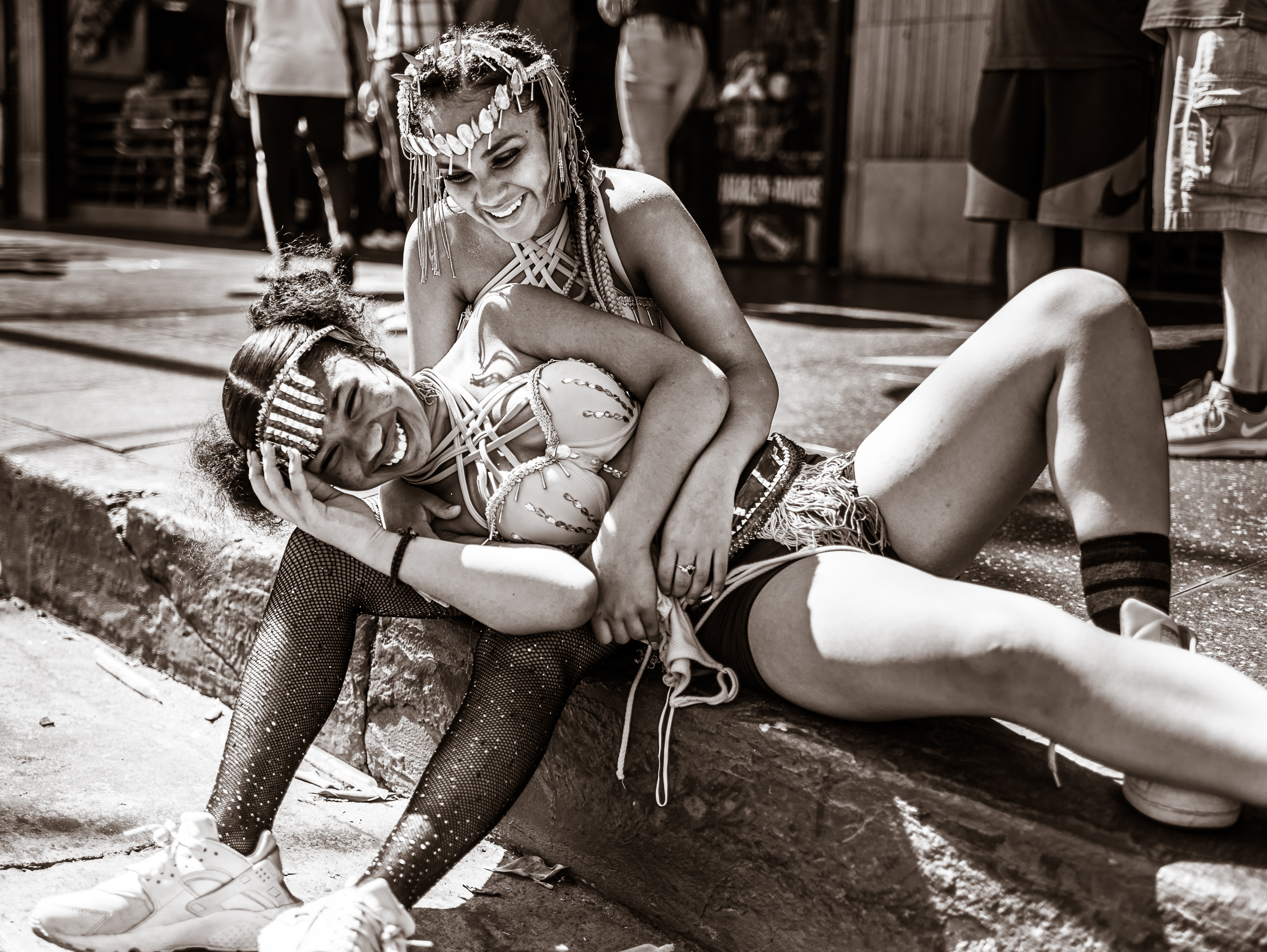 two dancers from the Hollywood Carnival Parade sit on the curb on Hollywood Blvd. One leans over and rests her head in the other's lap. They share tired, but real smiles.