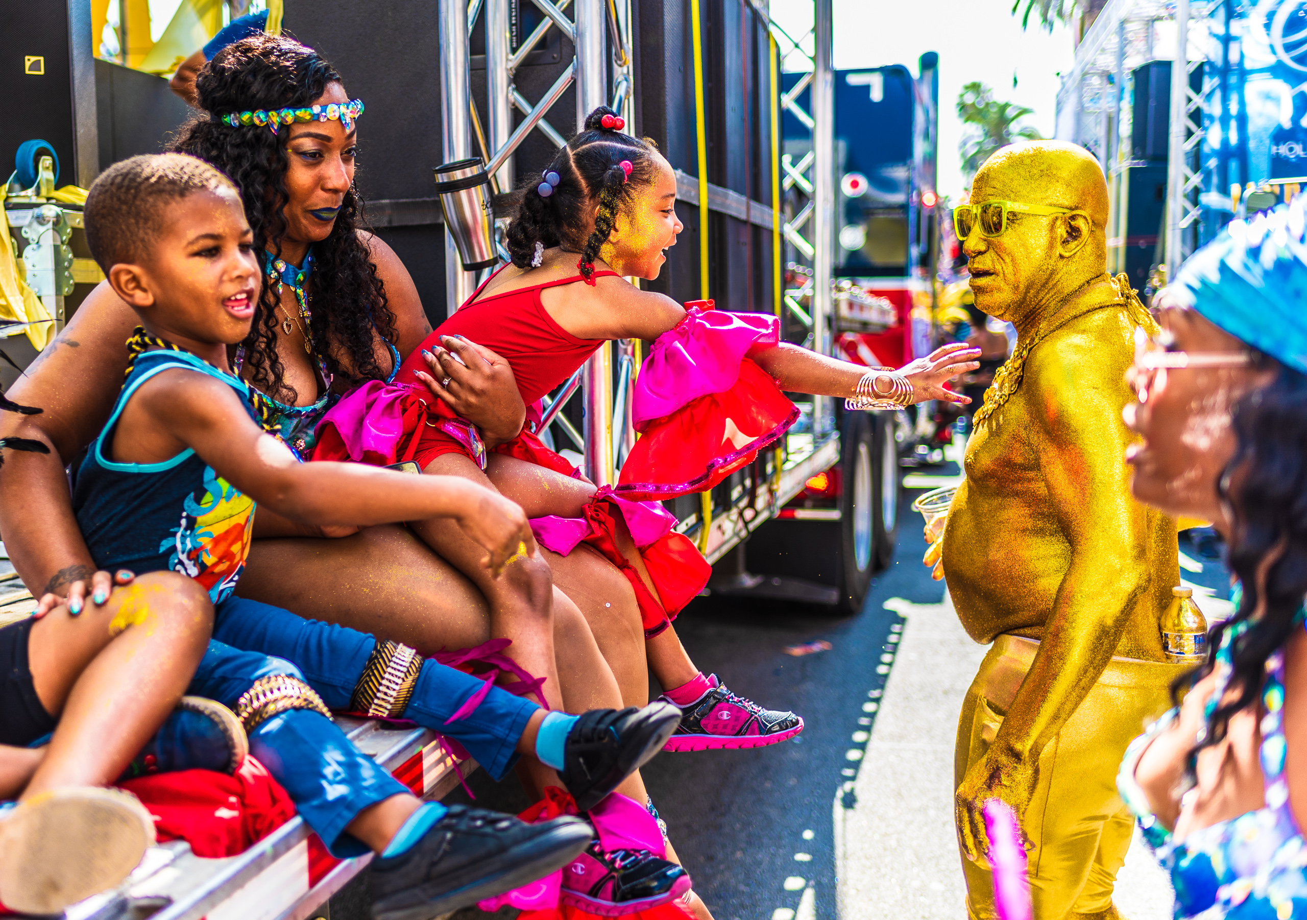 a young girl riding on a parade float reaches out to touch a man covered in shimmering gold color