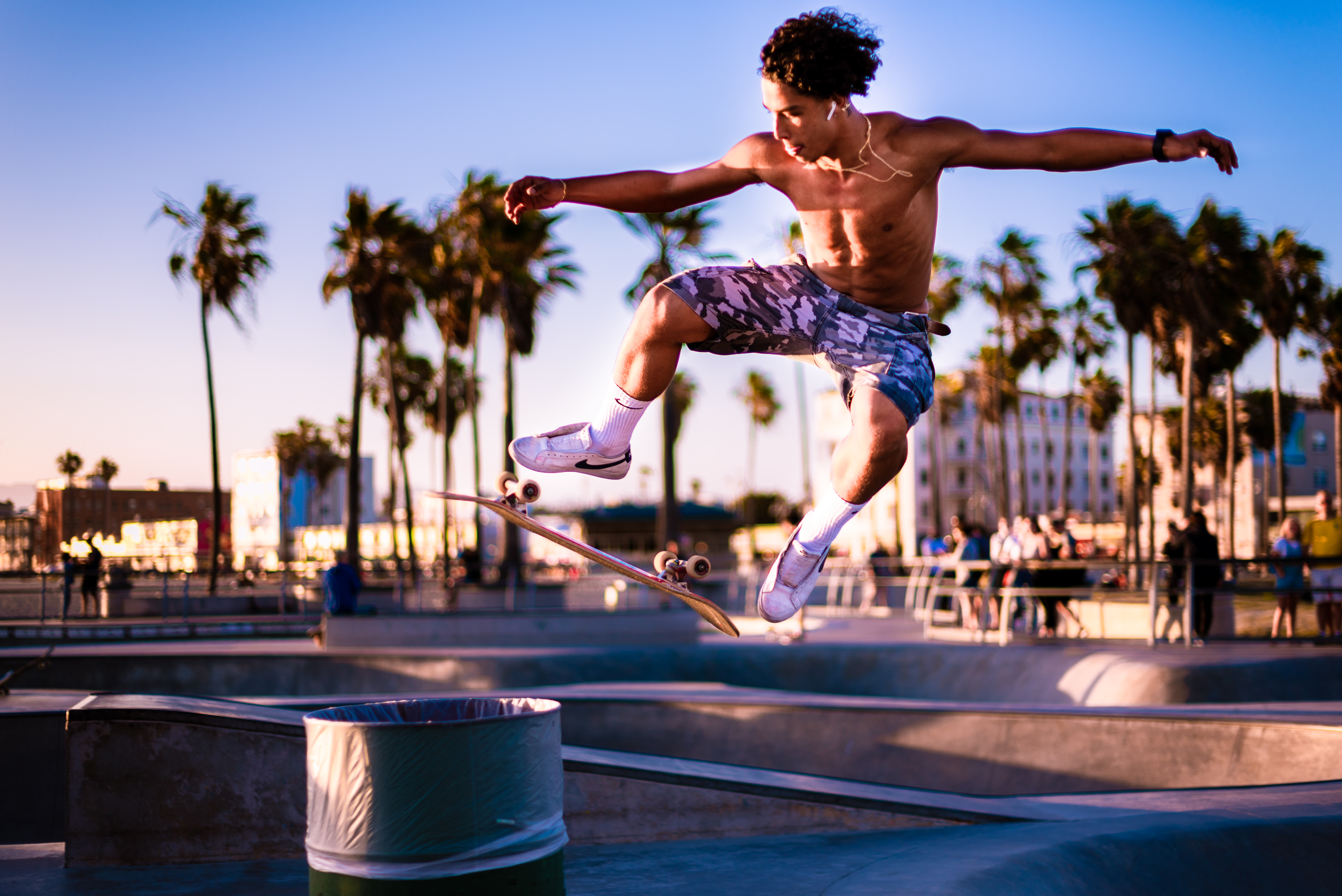 a skater at the Venice Skate Park leaps over a 55 gallon drum