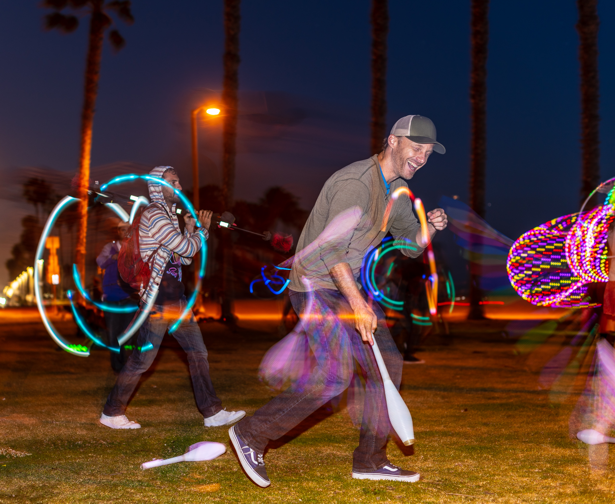 Morgan Bennett juggling LED Clubs in the dark at Venice Glow Flow in Venice Beach, CA