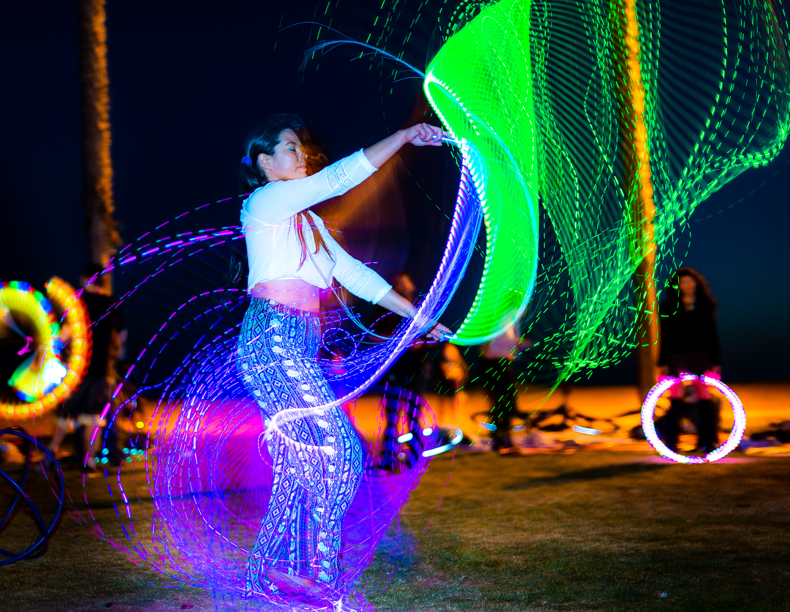 Bianca California performing with LED hula hoops and LED Pixel Whips at Venice Glow Flow at Venice Beach, CA