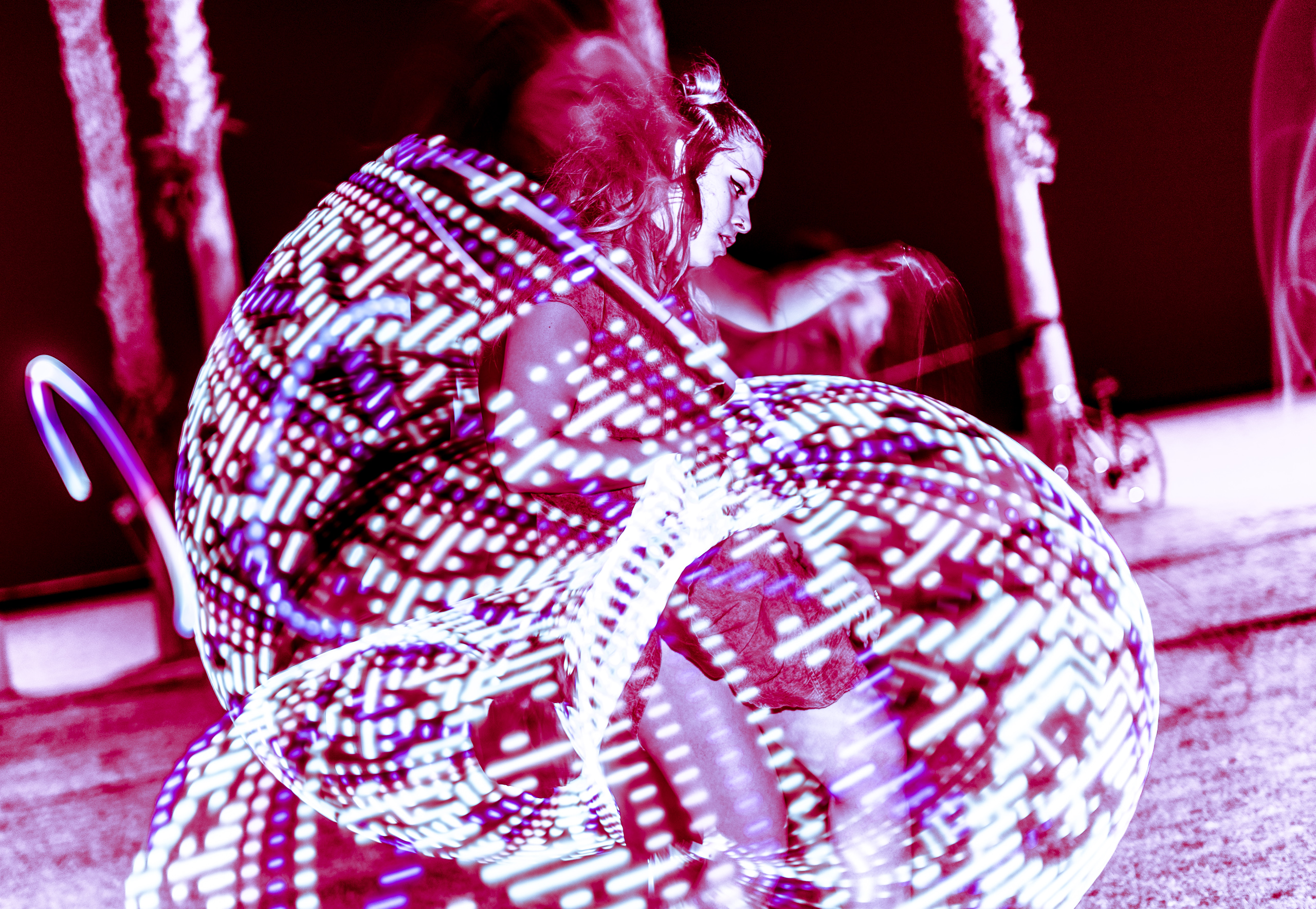 Alli Wolf, aka @wolfamongweeds, Los Angeles based DJ, Producer, Flow Artist, Techno, dancing with an LED hoop at Venice Glow Flow in the park at Venice Beach, CA