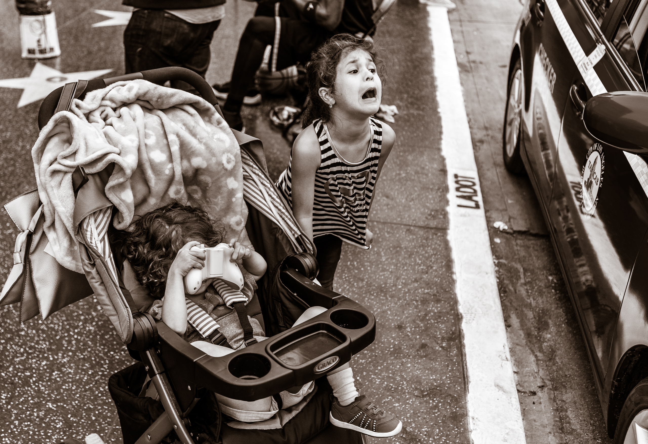 a young girl standing next to a stroller cries out in the direction of a curb-parked taxi cab